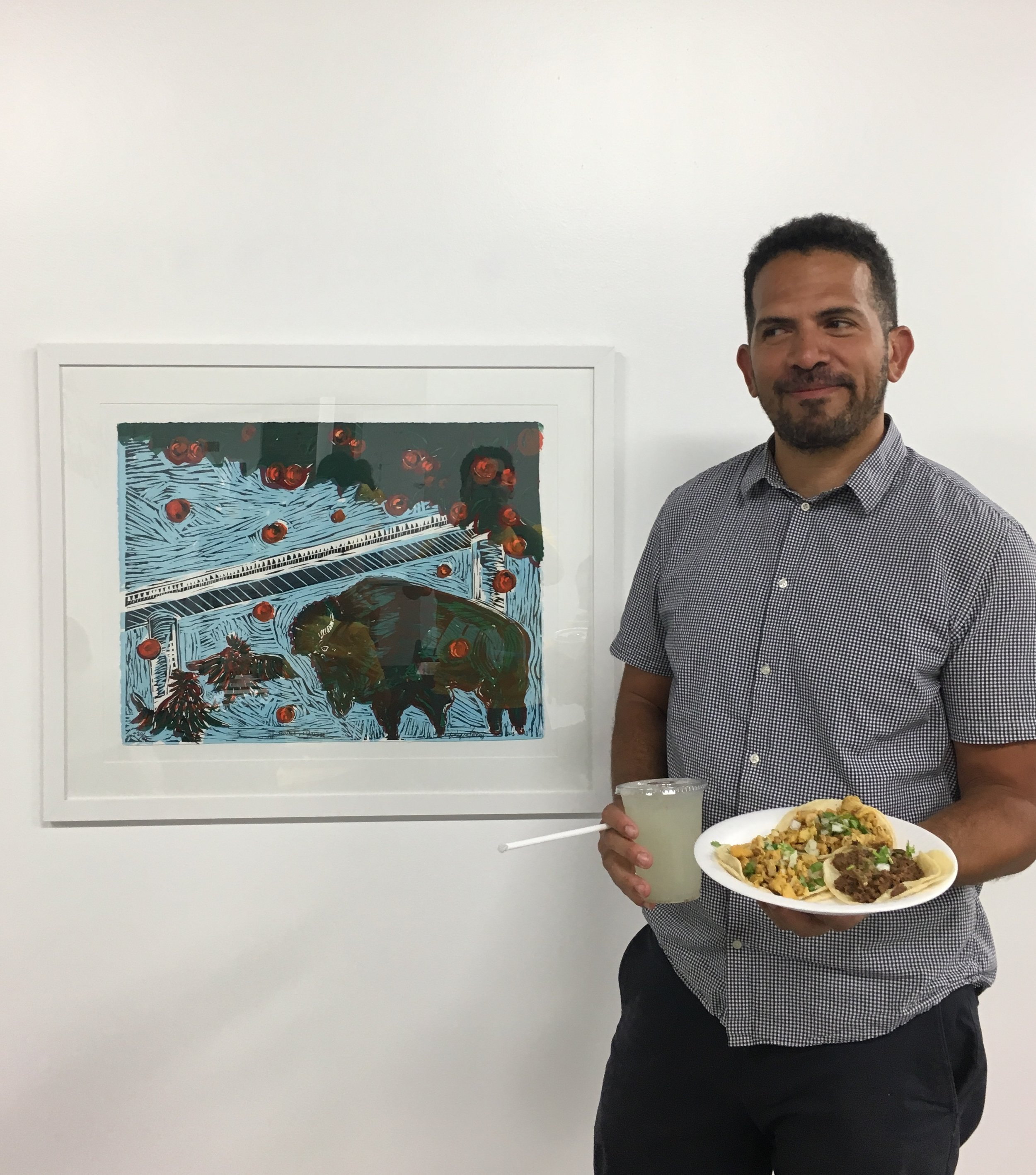 Artist Wayne Perry with tacos and drink, posing in front of  Trouble in Paradise.