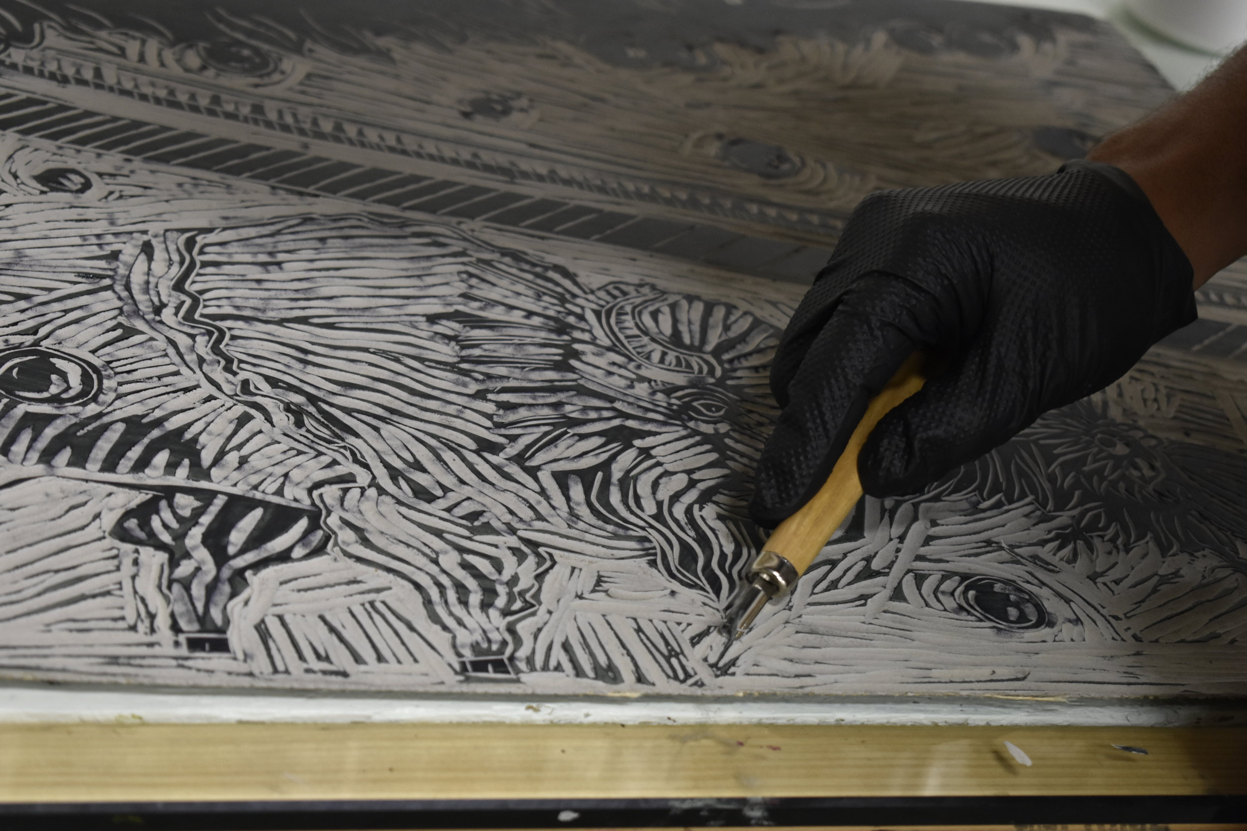Artist Wayne Perry carving out the linoleum block for his print  Trouble in Paradise.