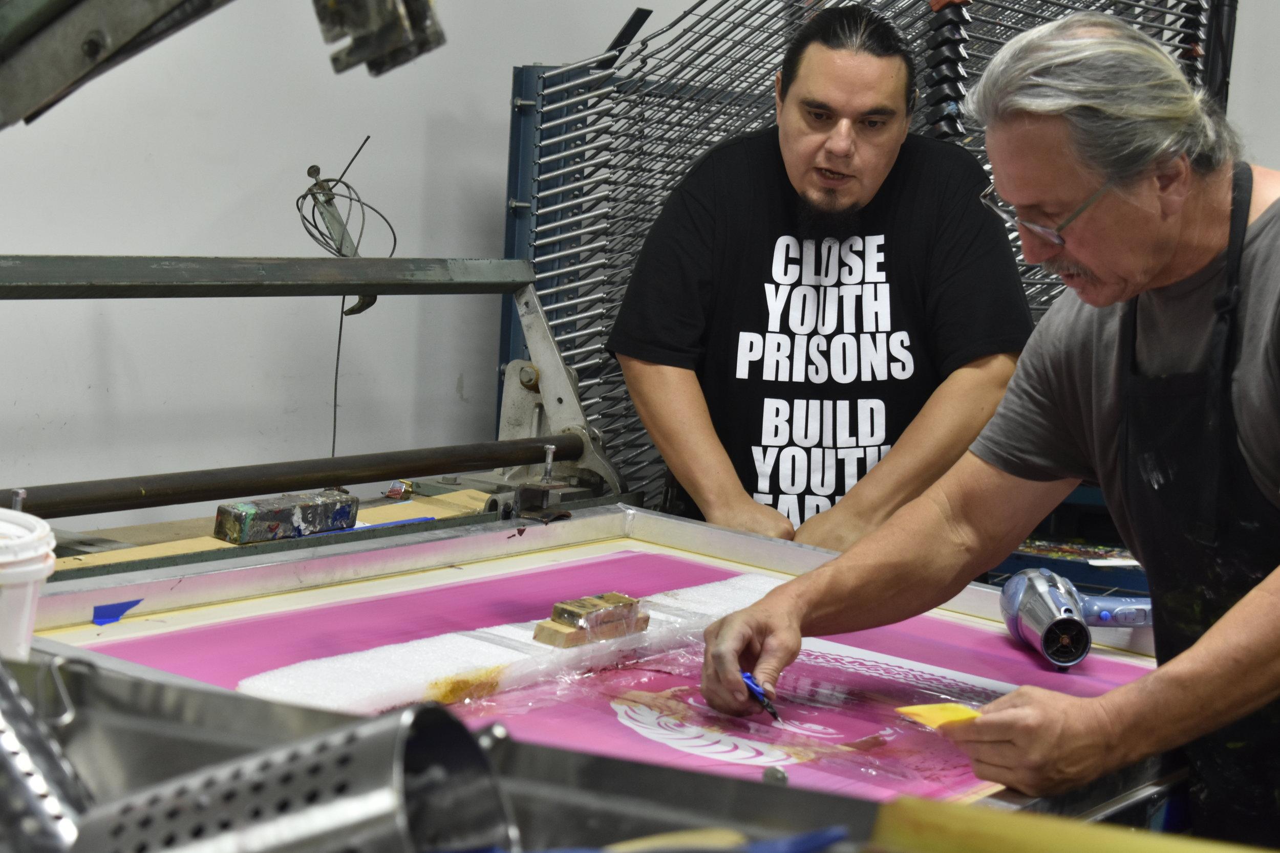 Master printer Oscar Duardo assisting Jesus Barraza with screen preparation for  Barbz.