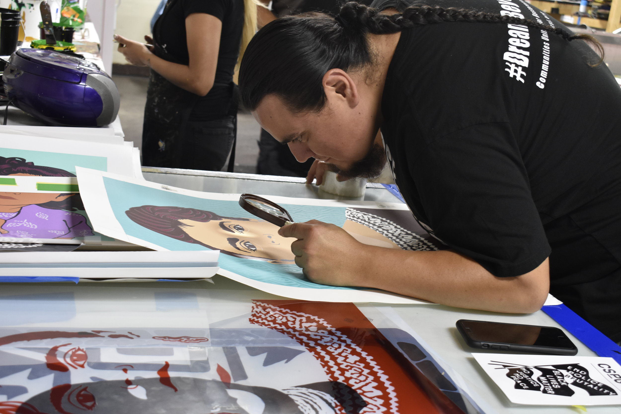 Artist Jesus Barraza from Dignidad Rebelde examines his print for quality and clarity.