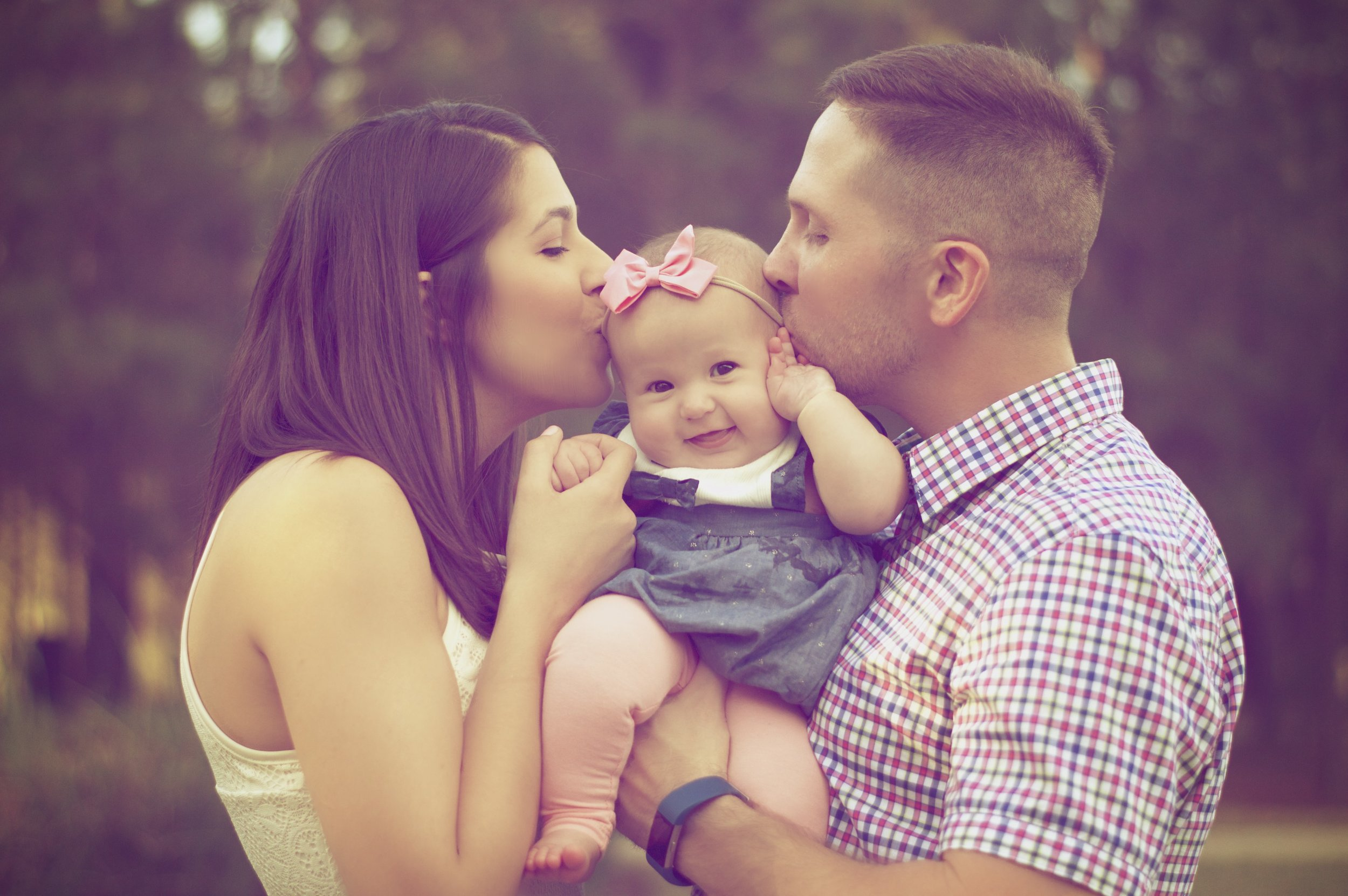 Couple Kissing Baby.jpeg