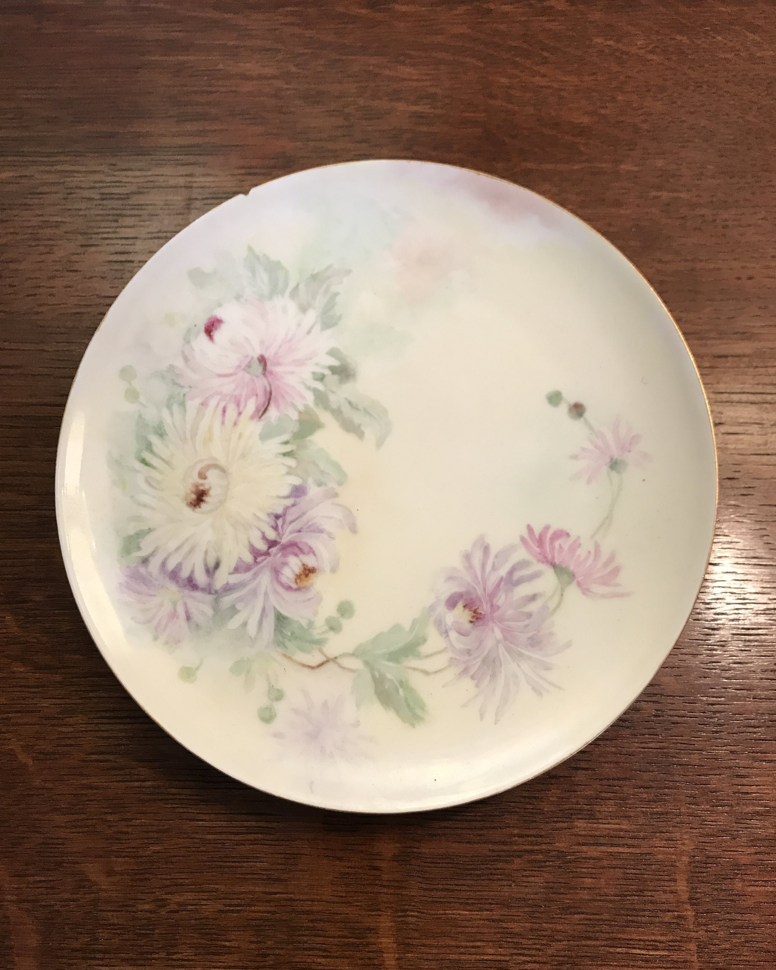 Haviland France Limoge Plate - Beautiful hand-painted dahlias on this French porcelain. The mark on the back was used from the 1890s to the 1930s. A similar plate with similarly painted dahlias online was dated 1920. There is a small chip and it carries a slight yellow patina. Plate hanger included..$20