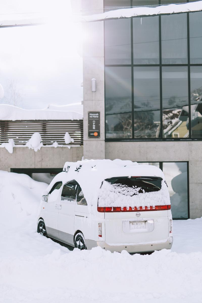 car covered in snow sun shining niseko japan.jpg