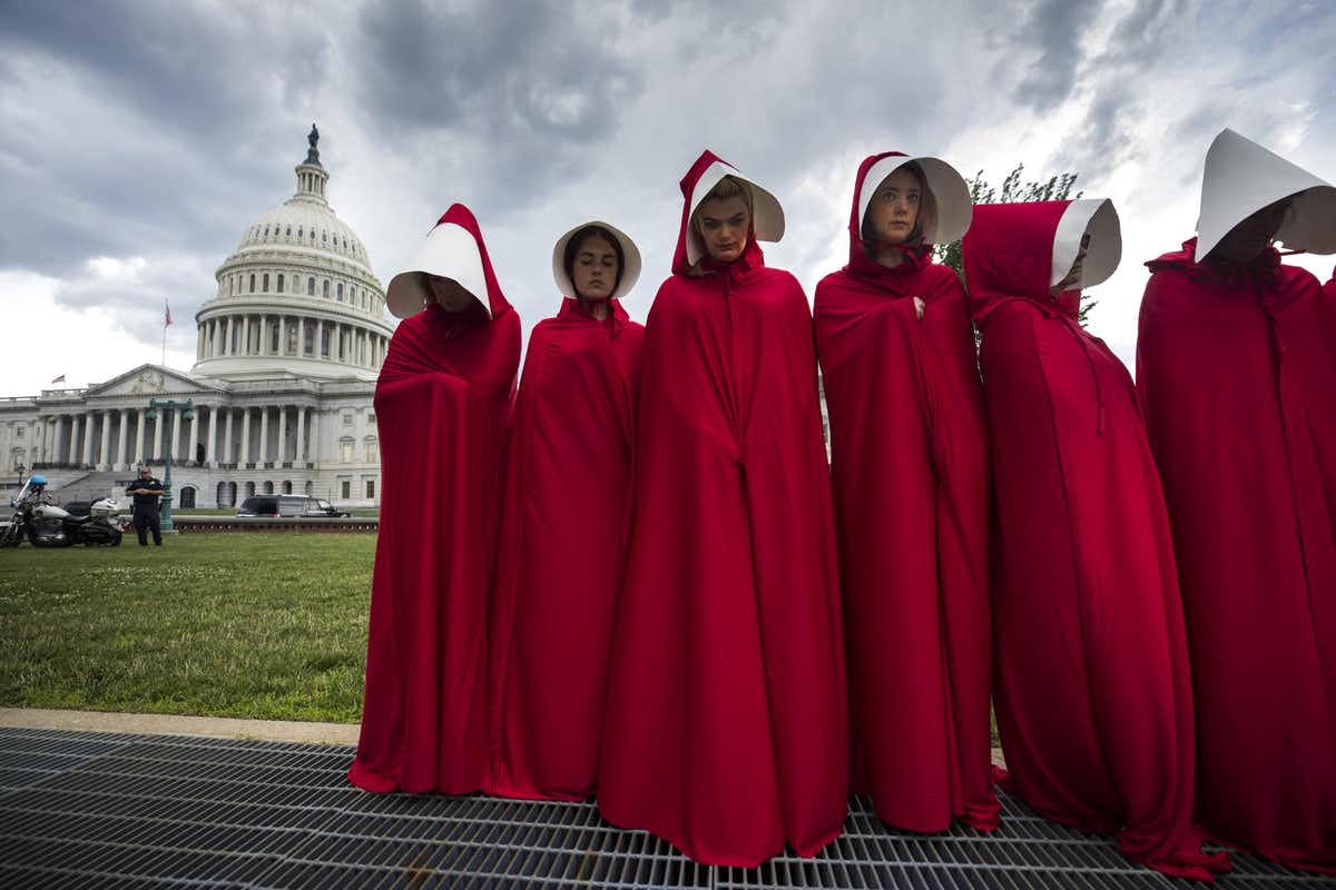 Activists in the U.S. have donned the red cloaks imagined by Margaret Atwood in  The Handmaid's Tale . Jim Lo Scalzo/EPA/AAP