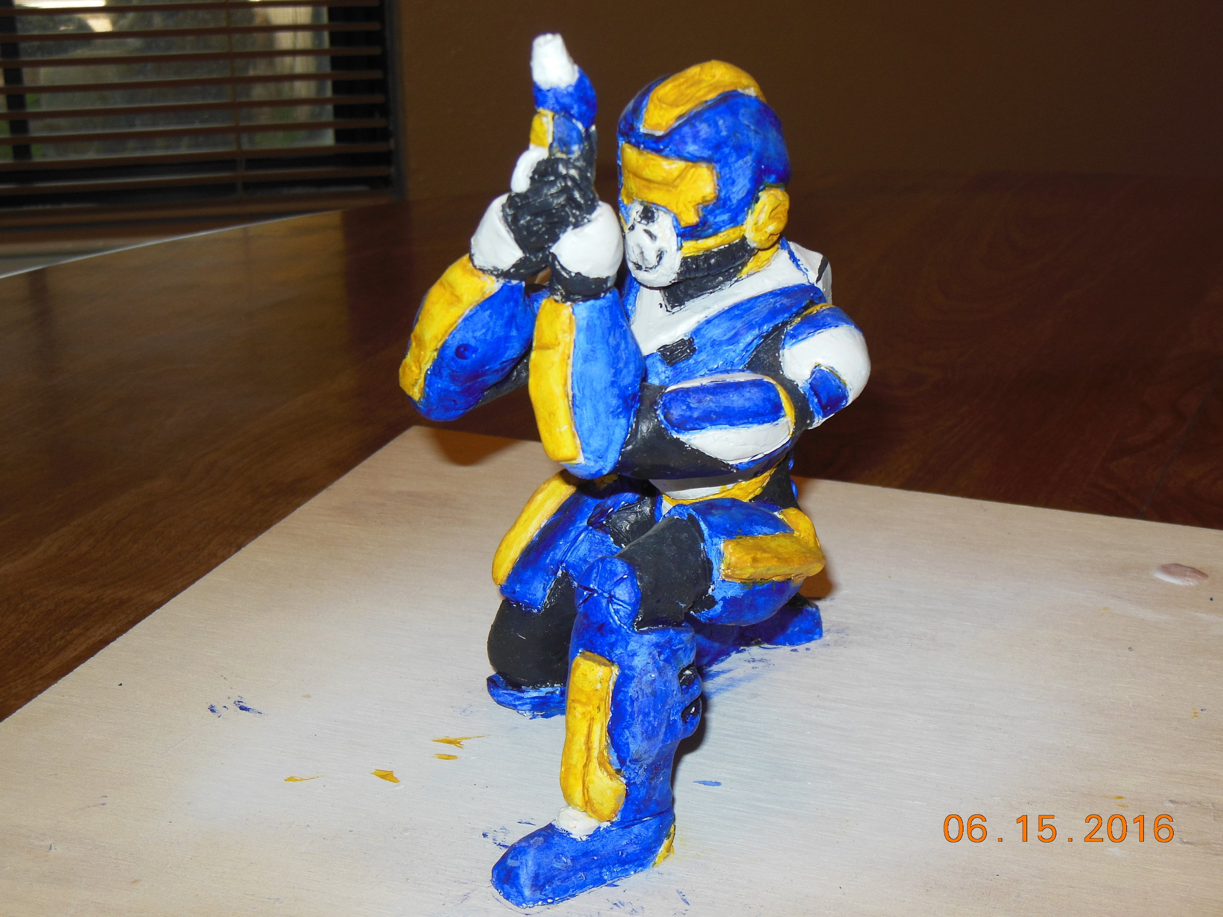A bounty hunter character sculpture I made. Referenced drawings to the side.
