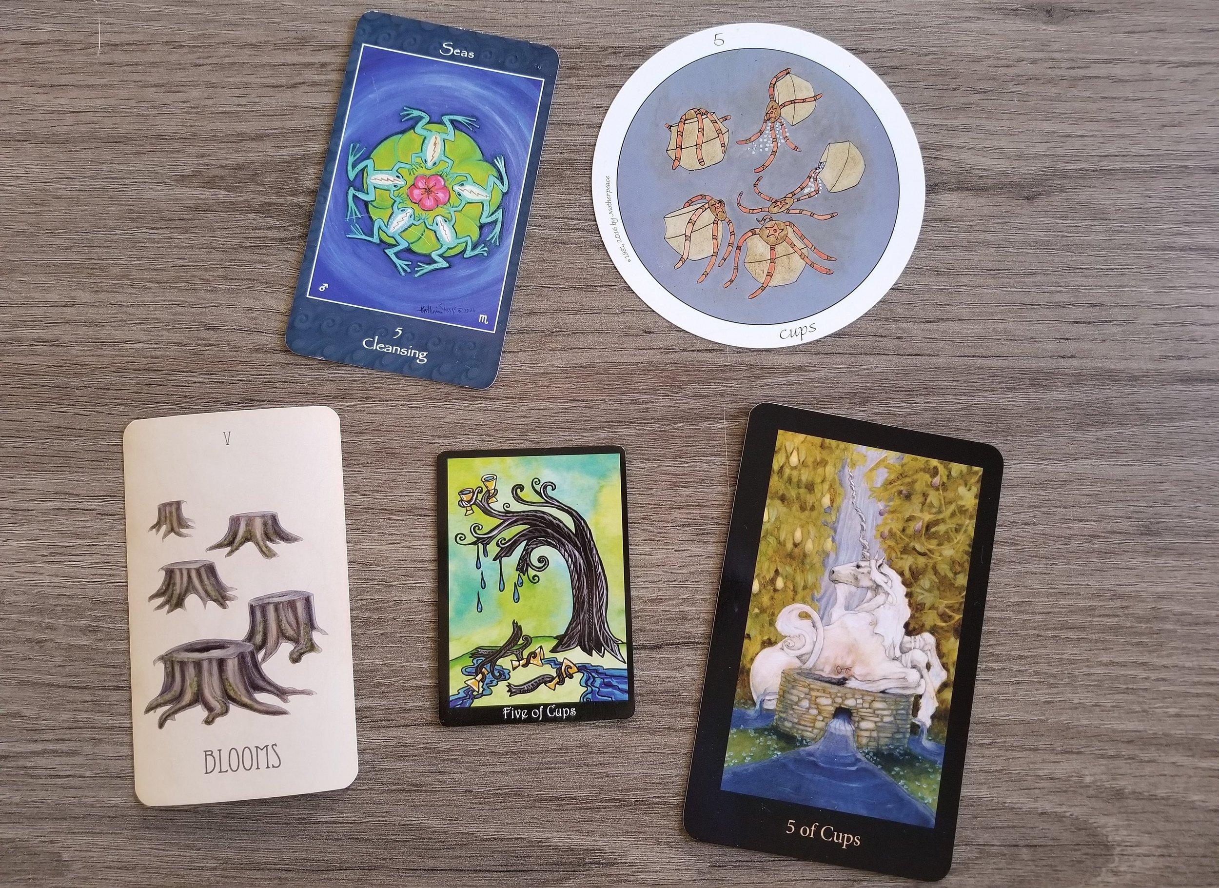 Five of Cups from the Mythical Goddess Tarot, Motherpeace Tarot, Wooden Tarot, Tarot of Trees, and Mary-El Tarot