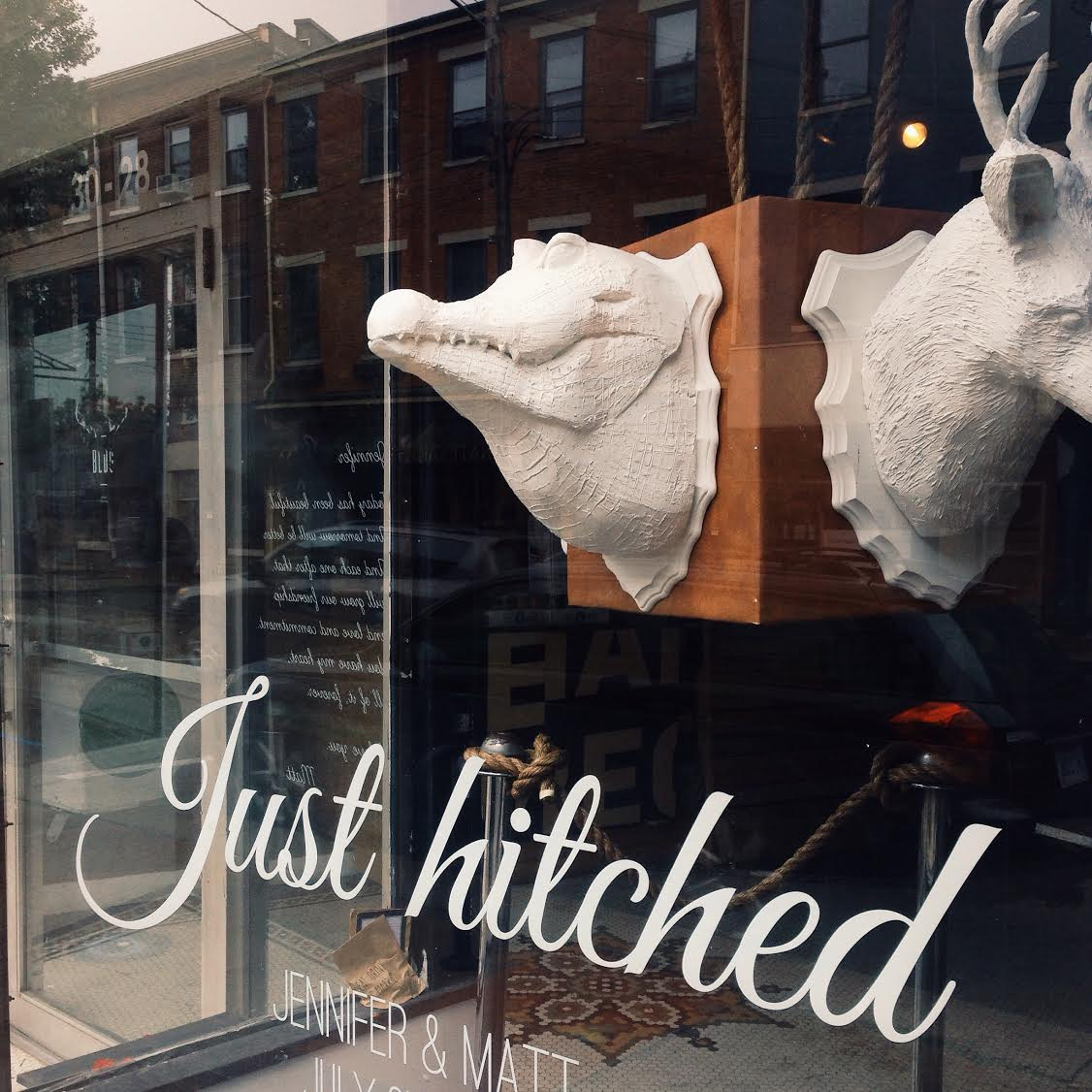 A window display created for a wedding reception. Each side showcases an animal that represents a piece of the couple's personal history.