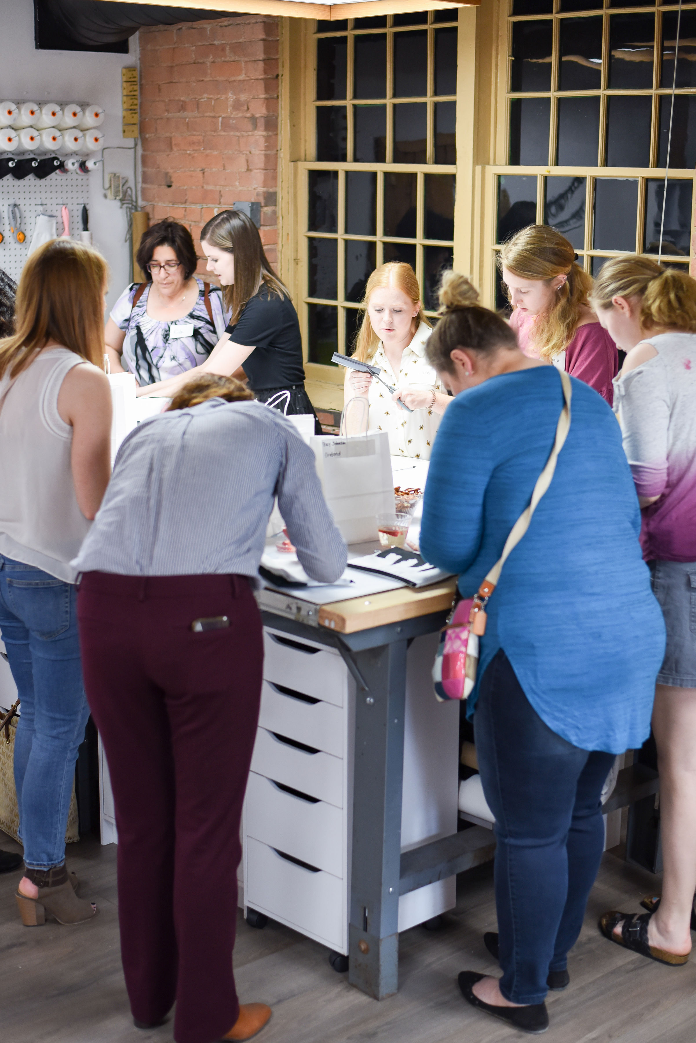 The ladies gathered around Anne's work station to create their monogram.  Photo by Stephanie Penick Photography.