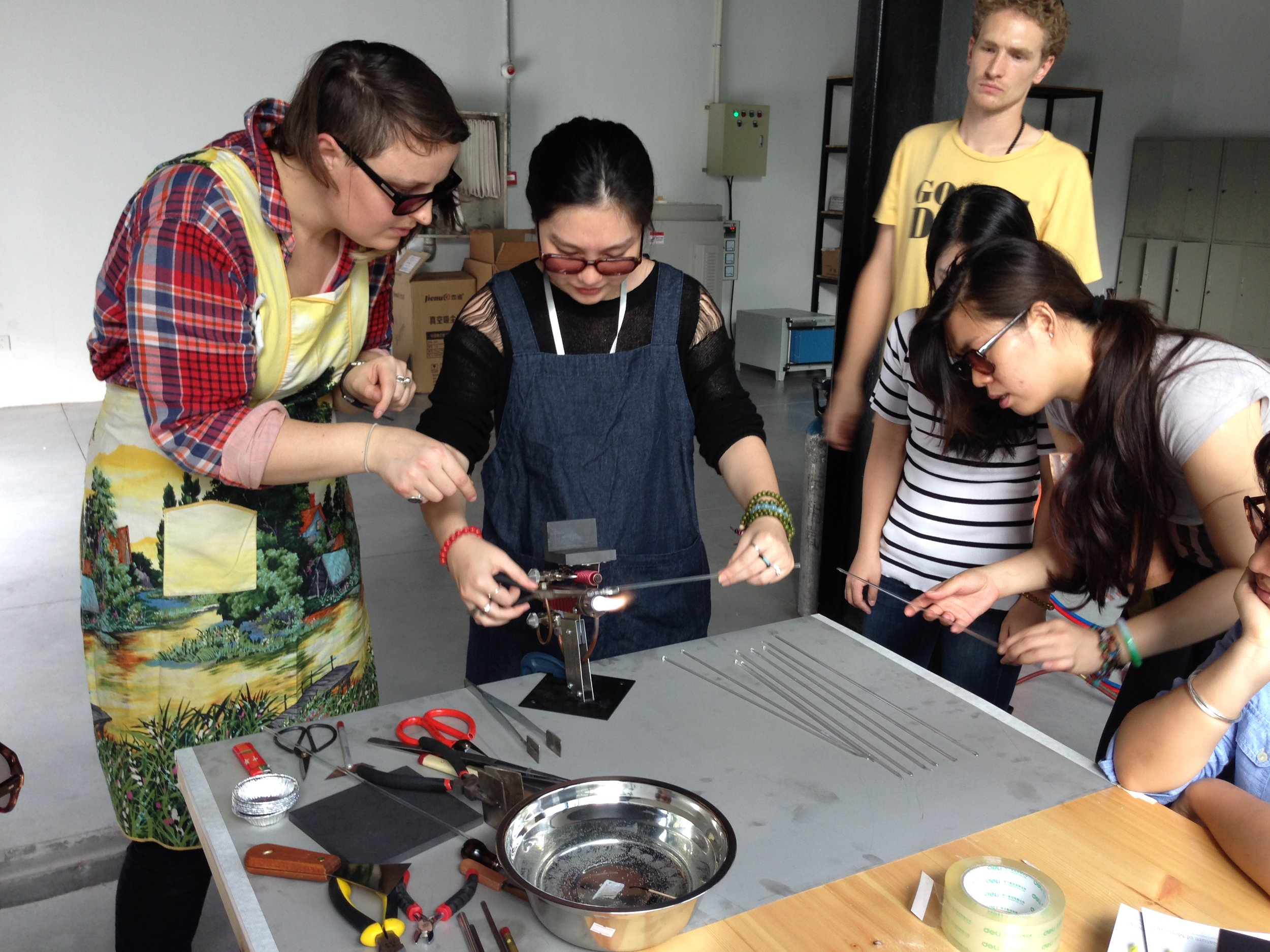 Jess Dare teaching students how to use a flame to manipulate glass at San W Studio