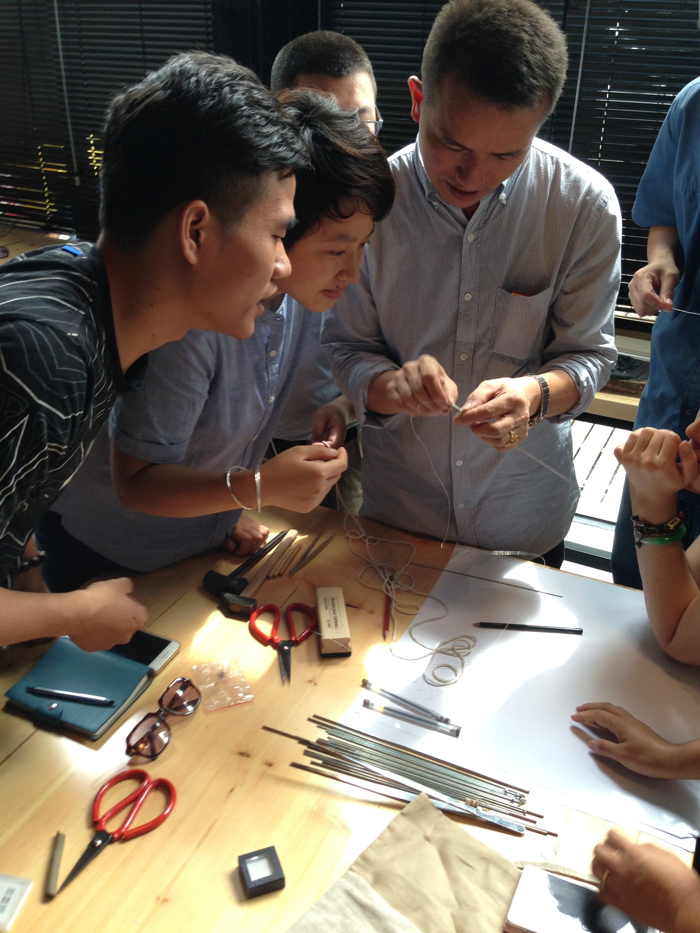 Workshop participants get in close to see the detail of Master Lie's skilled hands
