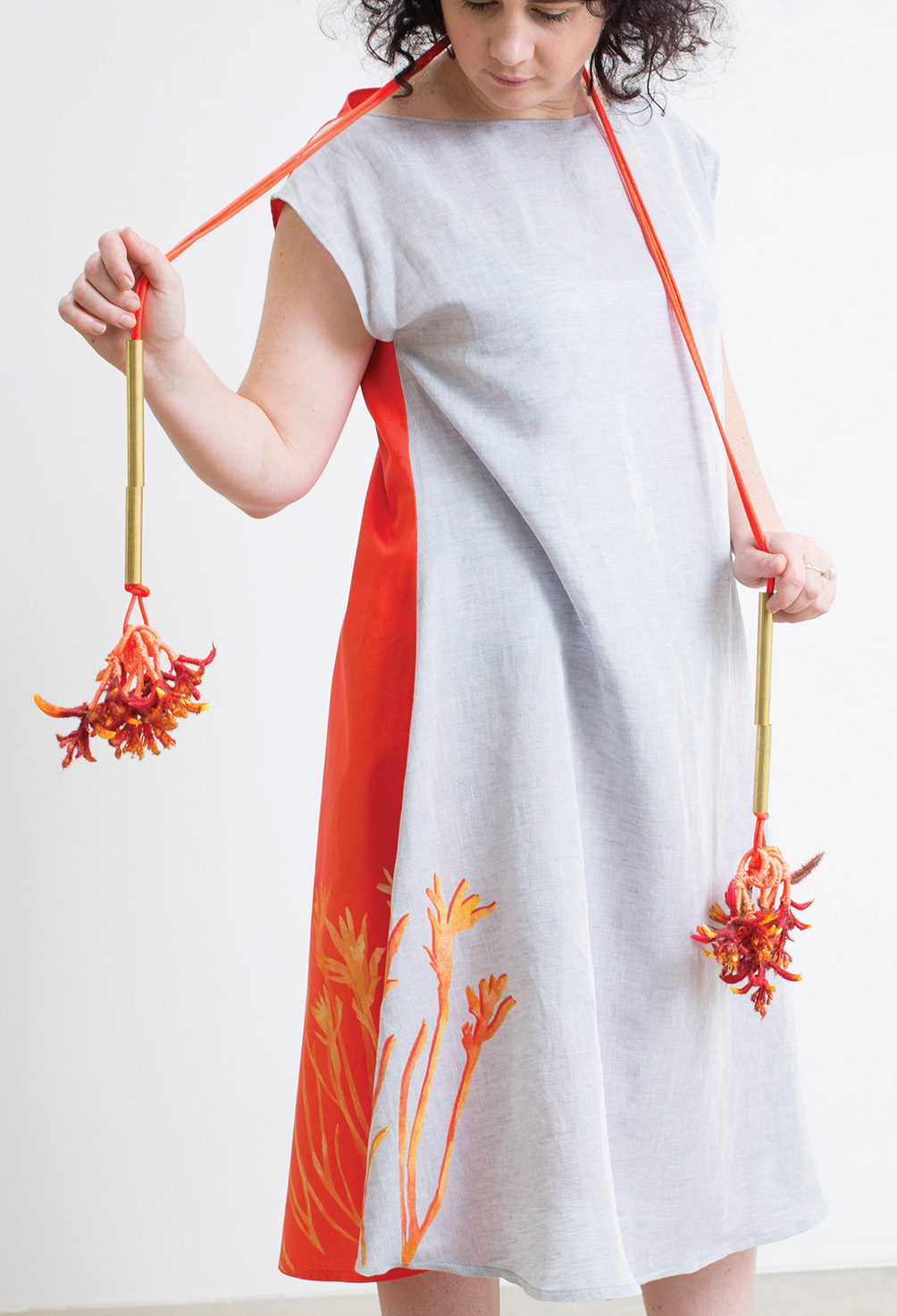 Kangaroo Paw Poi  2017, artificial foliage, brass, beads, thread, paint. Kangaroo Paw dress 2017, long grey and red linen-cotton, hand cut stencil print, one-off. Photographed by Craig Arnold