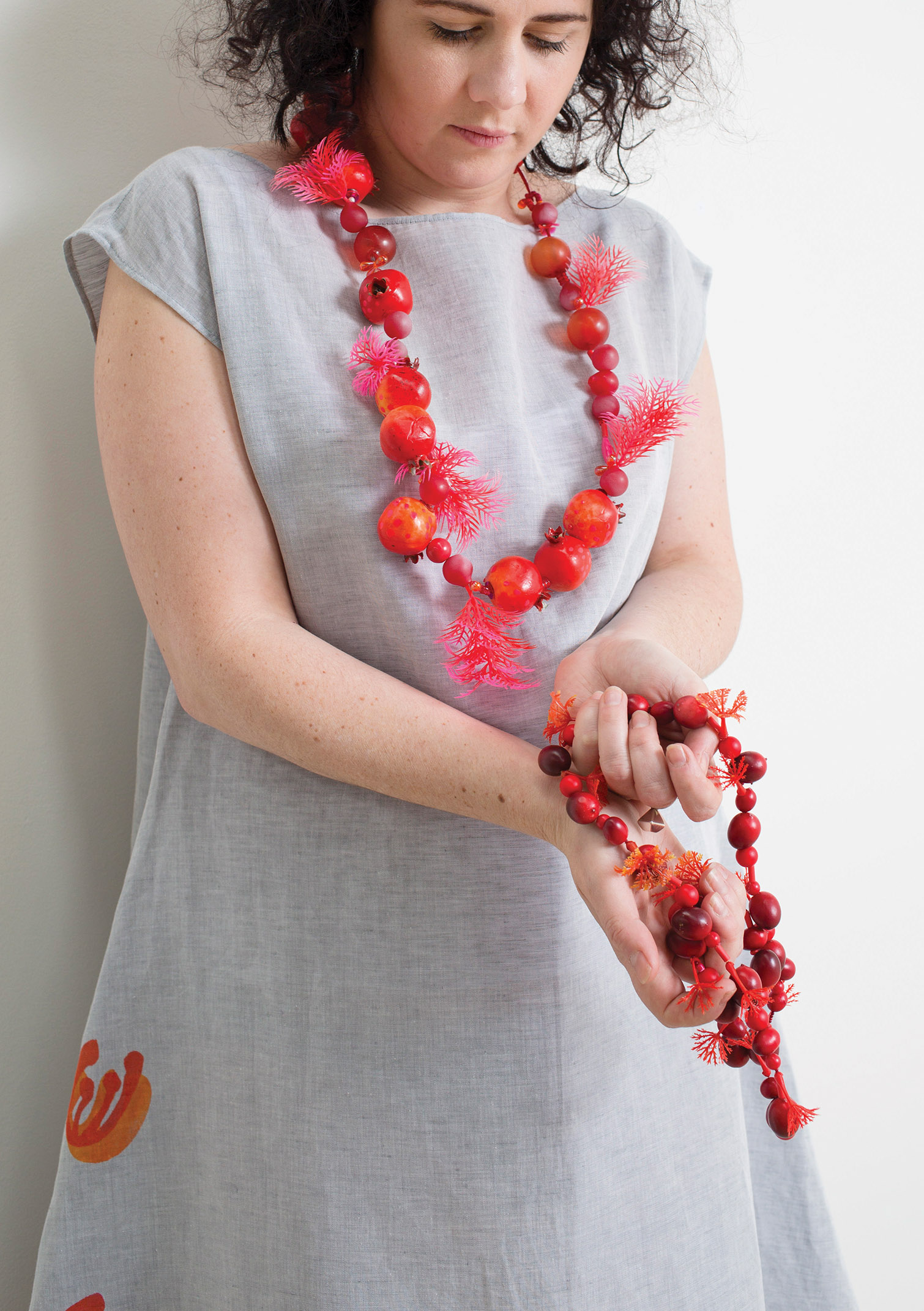 Pomegranate garland  2016, artificial foliage, beads, paint.  Berry garland  (in hands) 2016, Artificial foliage, beads, paint.  Protea dress  2017, long grey linen-cotton with red appliqué, hand cut stencil print, one-off. Photographed by Craig Arnold