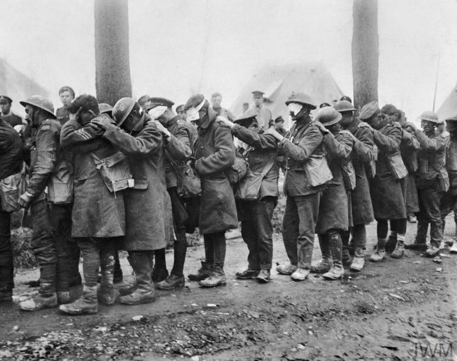 British troops, blinded in a gas attack during the Battle of Estaires, wait in line at an Advanced Dressing Station near Bethune, 10 April 1918