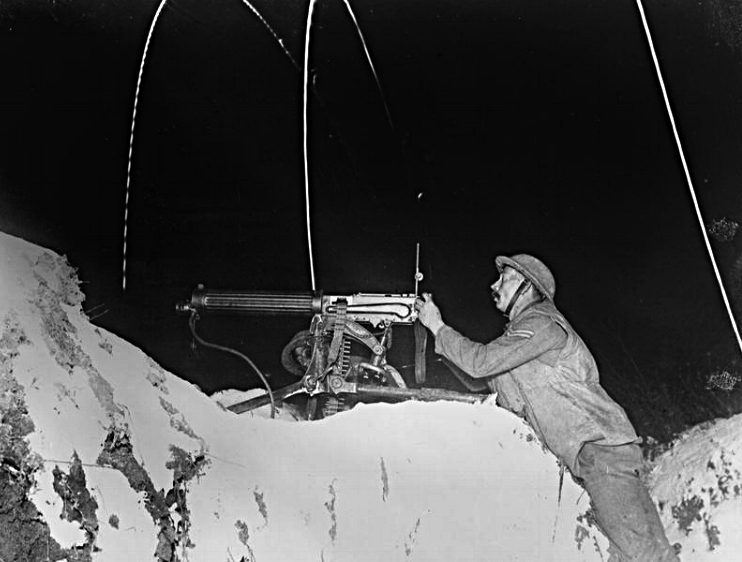 January 1918 photograph from the Western Front showing an Allied machine gunner firing on German communication trenches illuminated by British Very Lights