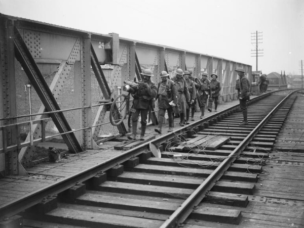 British troops crossing over a Merville railway bridge that has been primed with explosives in case the bridge needs to be destroyed, 11 April 1918.