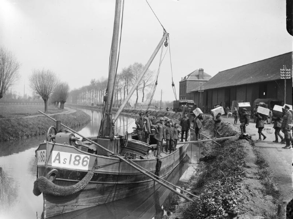 Men loading stores and munitions onto a barge on the canal at Merville to prevent them falling into German hands, 11 April 1918.
