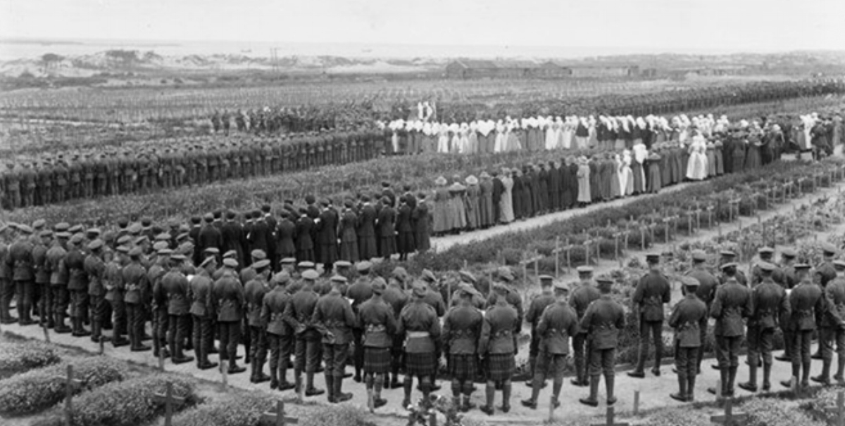Photograph taken by Henry Armytage Sanders recording the memorial service held at the Étaples Military Cemetery on 4 August 1918 commemorating the fourth anniversary of the start of the First World War. Many of those attending – civilians, nurses and military personnel – stand amongst the recently dug war graves.