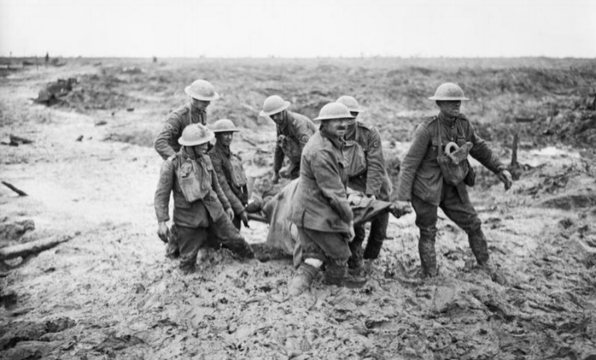 A team of stretcher bearers struggle through deep mud to carry a wounded man to safety during the Third Battle of Ypres.