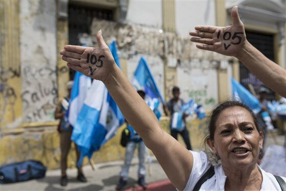 "Protesters show their hands with a number ""105"" in reference to the votes needed in Congress to lift President Jimmy Morales' immunity in Guatemala City on Sept. 11, 2017.Moises Castillo / AP"