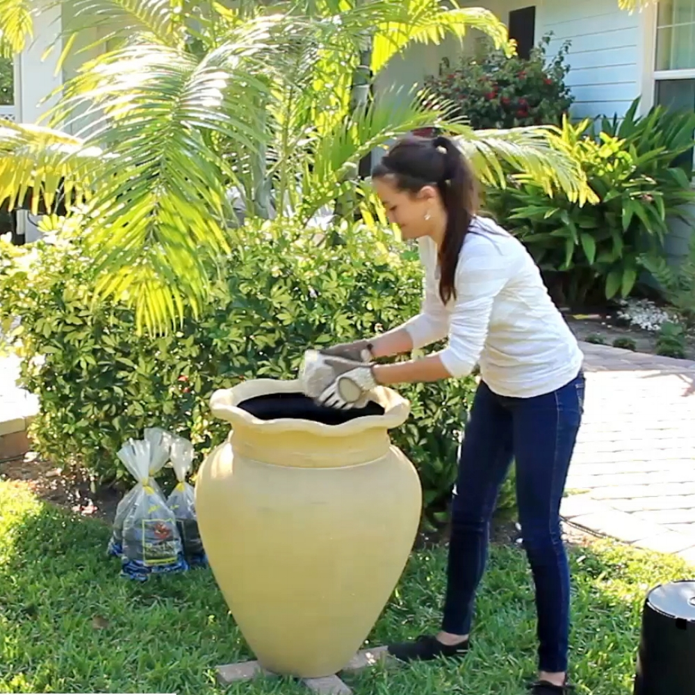 Step 6 - Once the planter is positioned, add the 6 pavers into the planter. Notice that your assembled TotalPond® Container Fountain Kit with Light is draped over the back of the planter. Place a black planter with no holes over the pavers to conceal them.