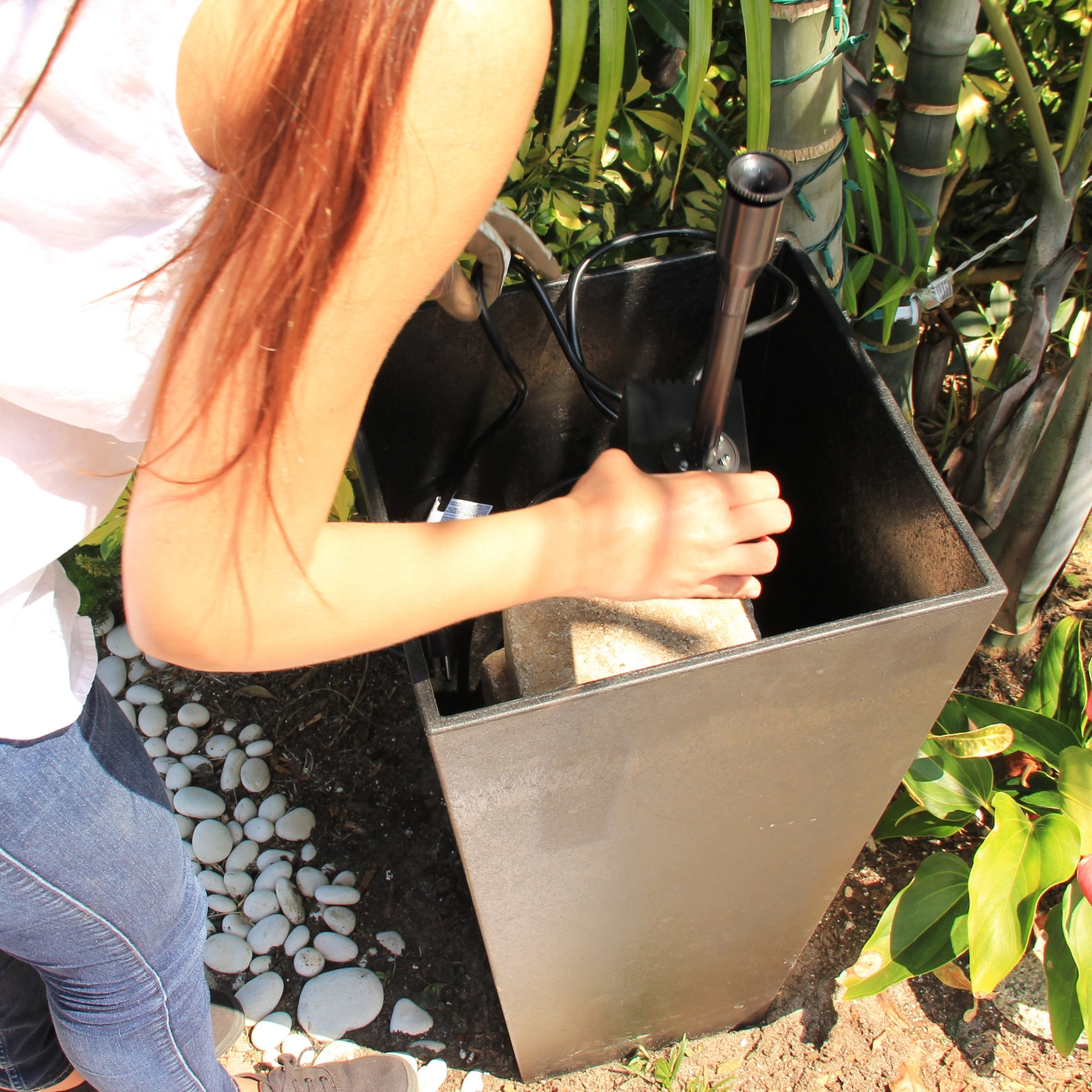 Step 4 - Assemble the Container Fountain Kit with Light and place it on the pavers. Run the cord down the planter and out the hole in the back.