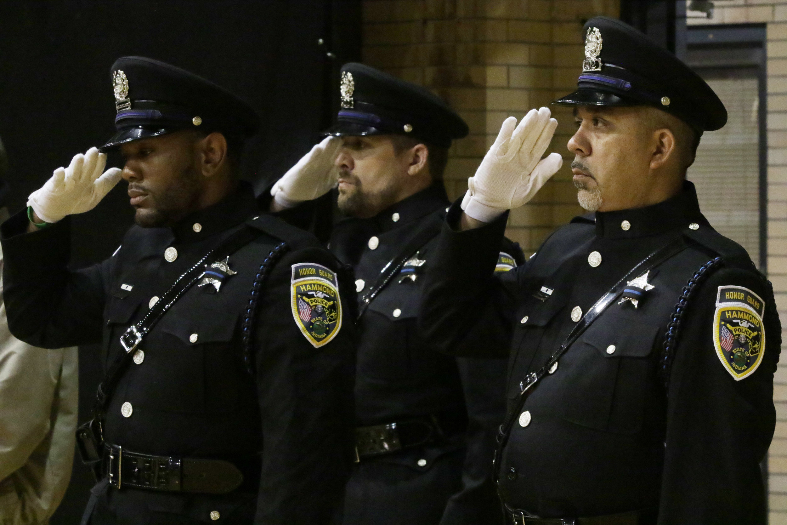 From left, Hammond Officer Jay Woods, Cpl. Ryan Orr and Cpl. Joseph Martinez salute during the national anthem at the Fraternal Order of Police Hammond Lodge #51 Annual Memorial Service at the Hammond Civic Center.