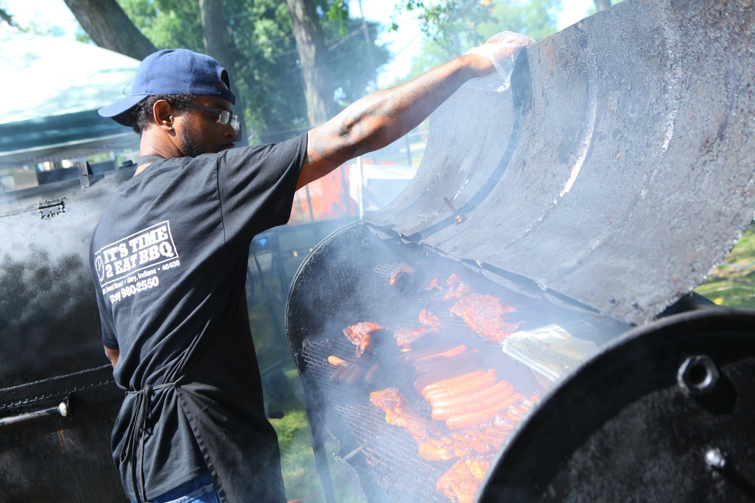 William Campbell, of Gary, checks on barbecue meats in a smoker belonging to It's Time 2 Eat BBQ at the Broad Street Blues Fest in Griffith, Indiana.