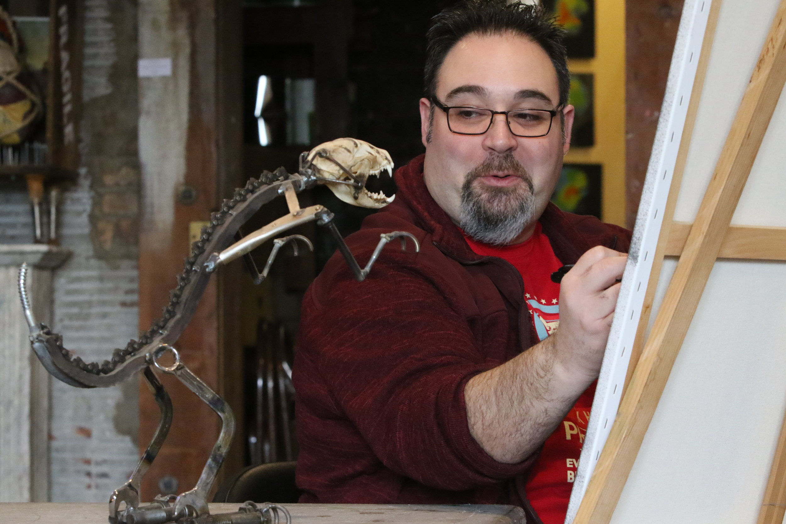 "Chris Guzman, a curator at Paul Henry's Art Gallery in Hammond, Indiana, smiles as he translates the likeness of ""Two Cent Cindy"" onto a canvas."