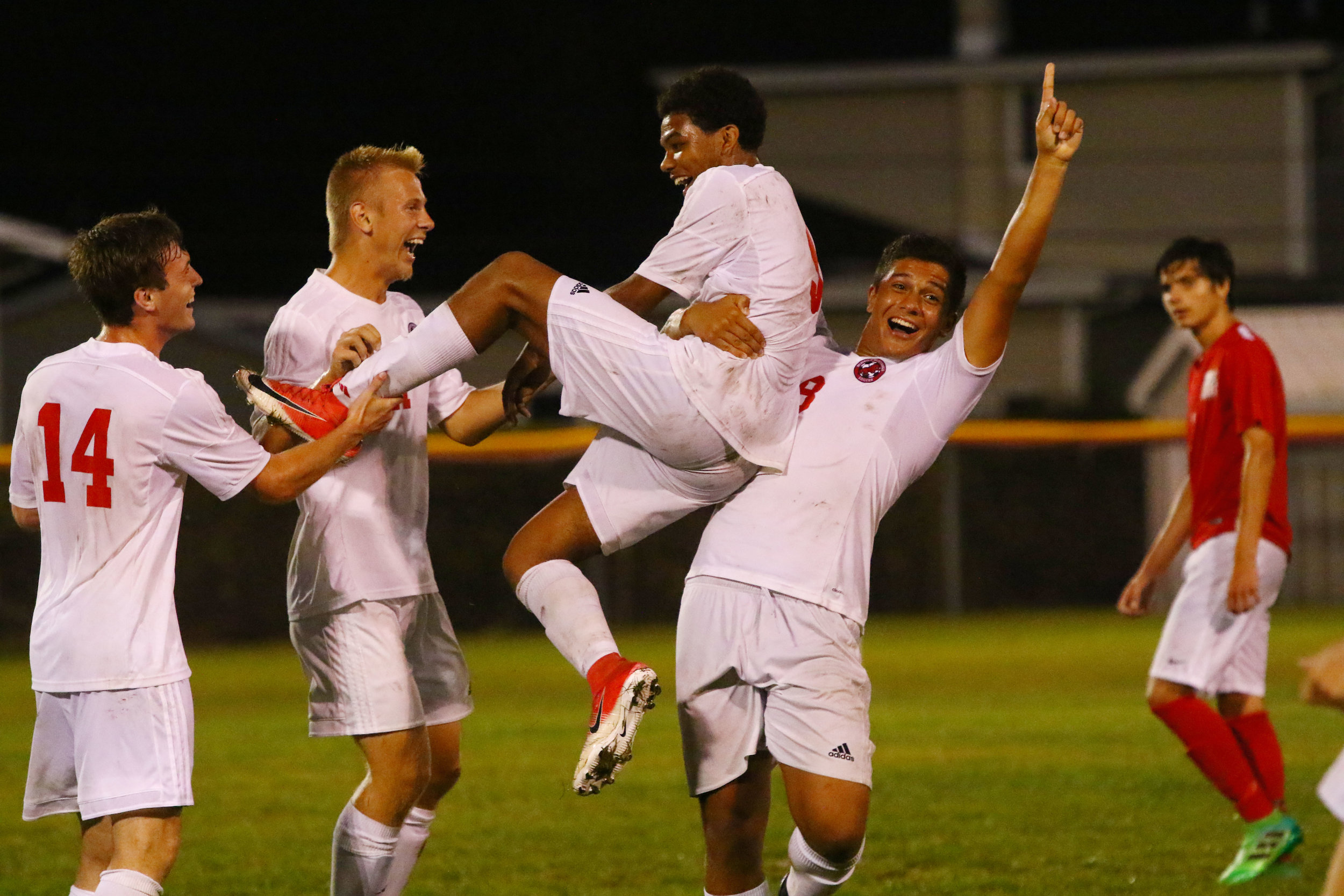 Munster's Evan DuBose, center, is hoisted after he scored the fifth goal for the Mustangs against Crown Point in Munster.