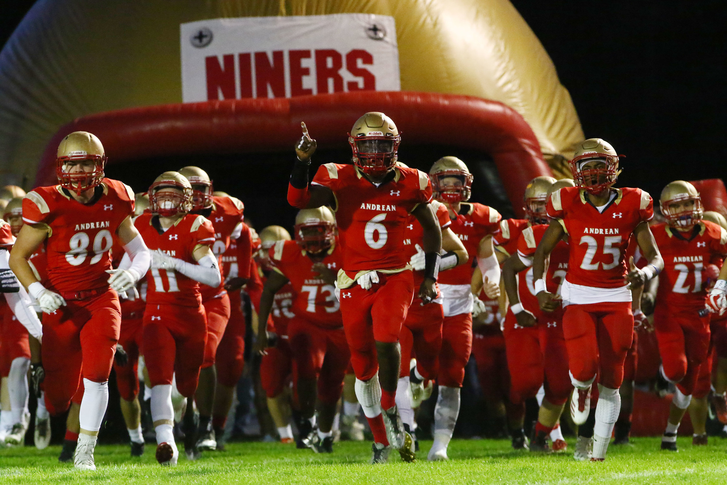 The Andrean 59ers run onto the field before a game against Kankakee Valley in Merrillville.
