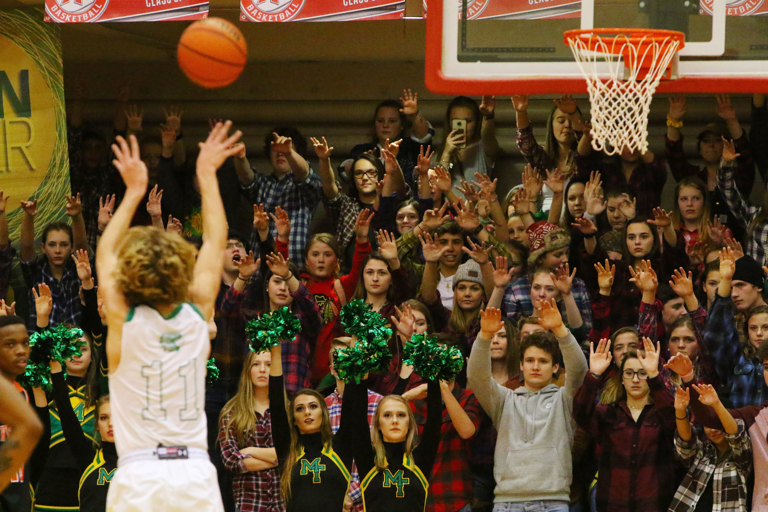 Morgan Township fans raise their hands as Trevor Braden knocks down a free throw during the Porter County Conference Tournament finals in Hebron.