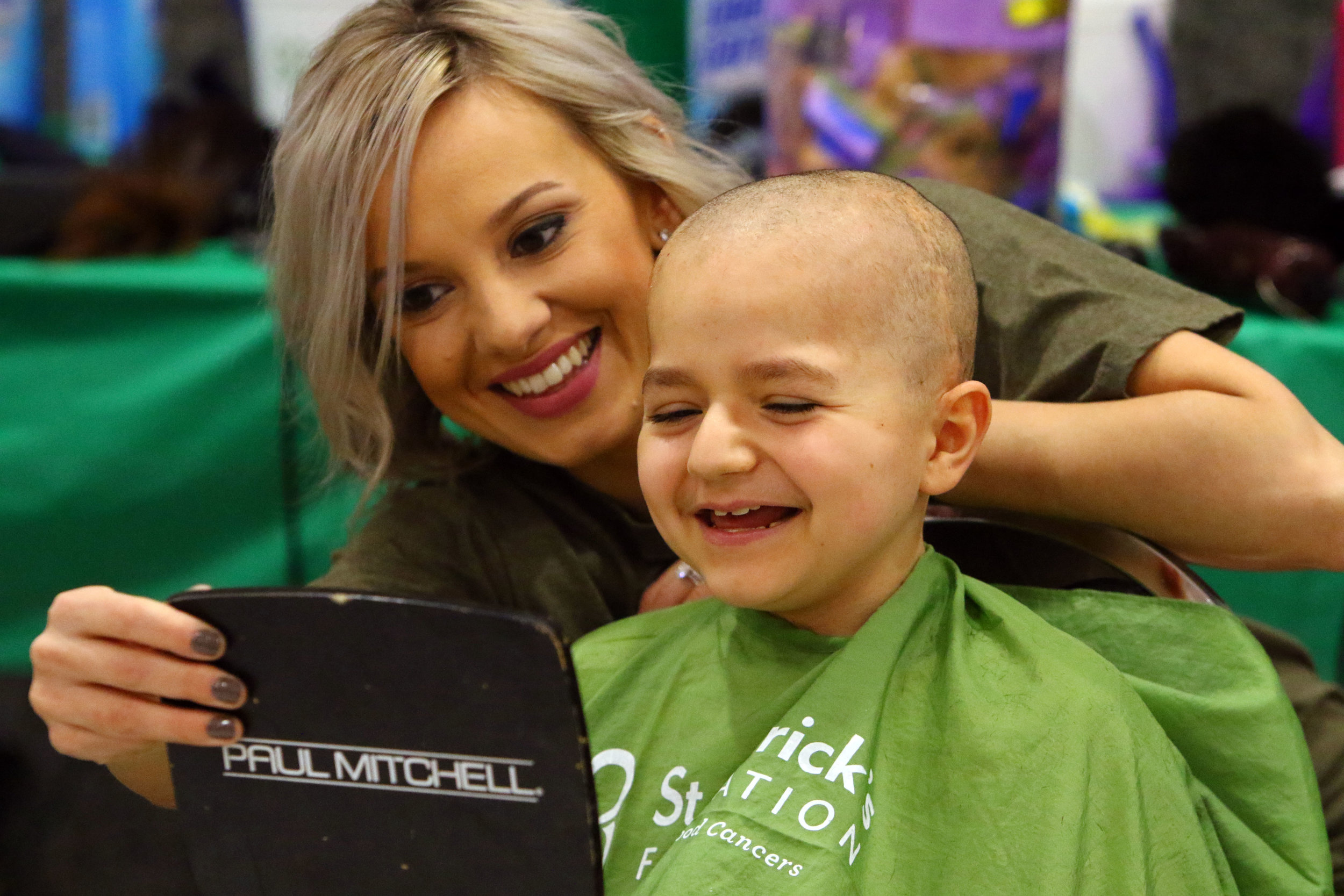 Michael Fogus, of Merrillville, checks out his reflection in the mirror after having his head shaved at the Northwest Indiana Cancer Kids Foundation 7th annual St. Baldrick's event in Merrillville. Fogus is a two-time brain cancer survivor. His family attended together to all go bald.