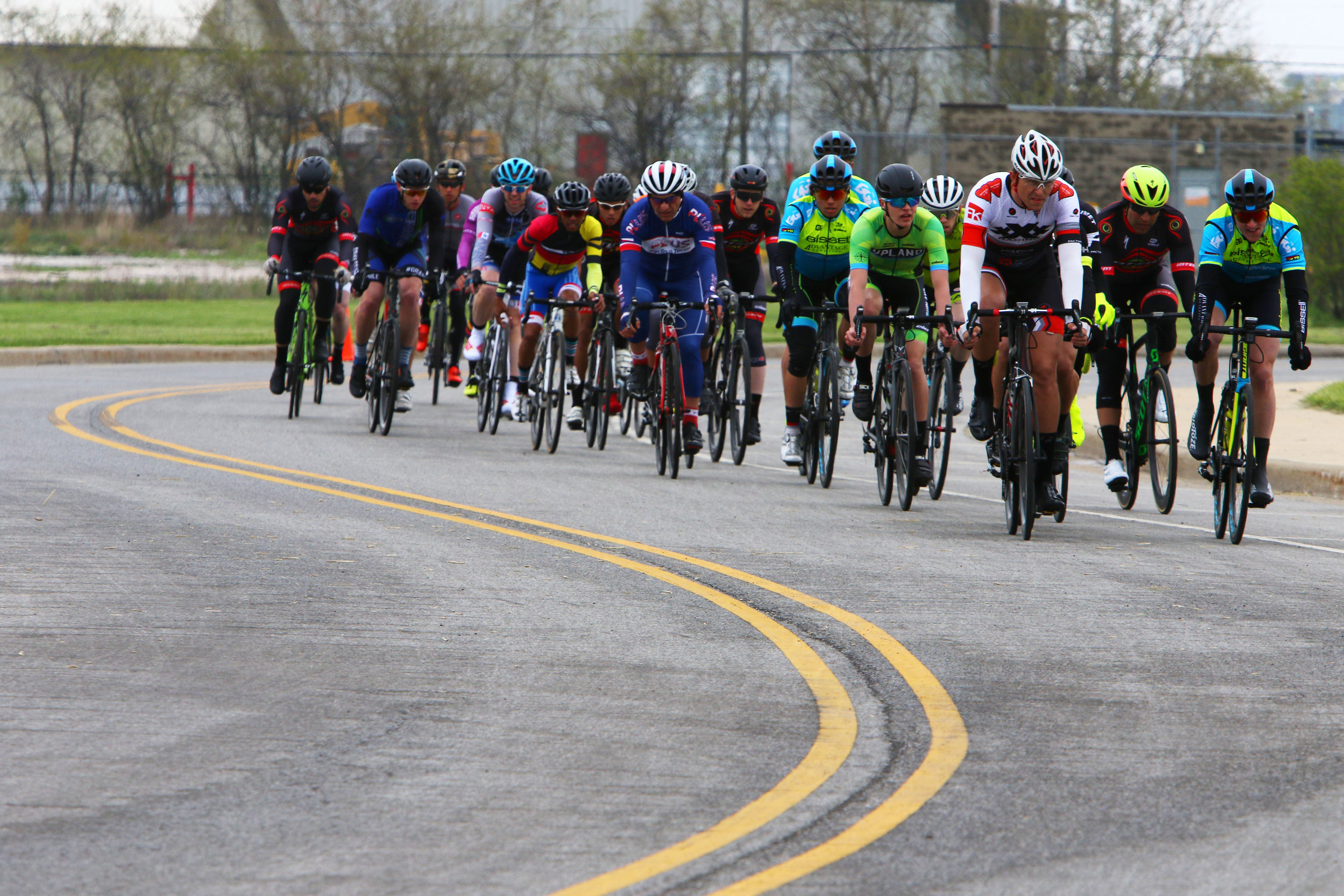 Participants in the men's pro race ride through the course at the Region Riot Criterium bike races at Wolf Lake Pavilion in Hammond.