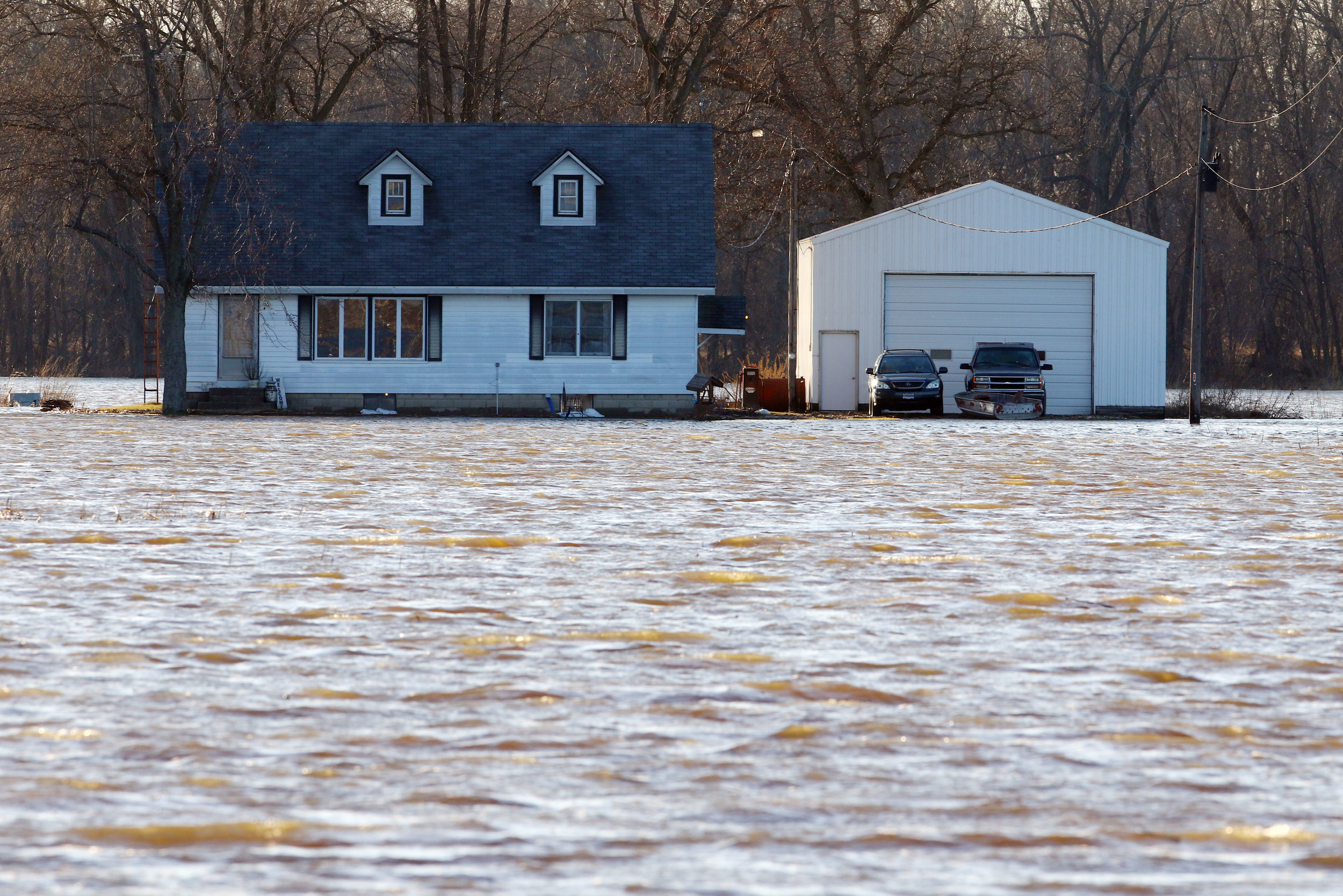 A home is surrounded by water in a flooded field near DeMotte.