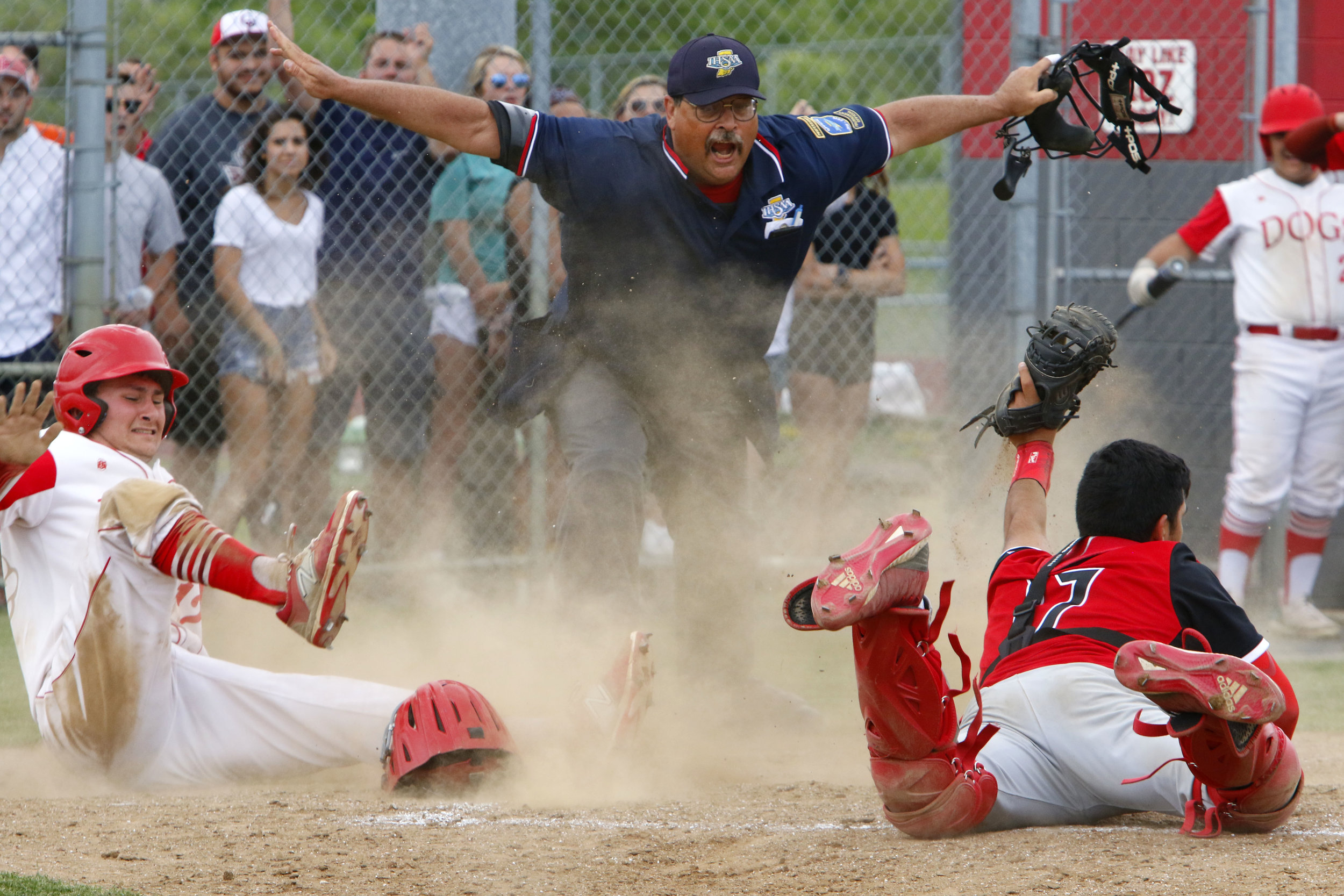 The umpire calls Crown Point's Drew Horton, left, safe at home plate after Portage's Xavier Alvarez tried to get the out against the Bulldogs during a 4A sectional title game in Crown Point.