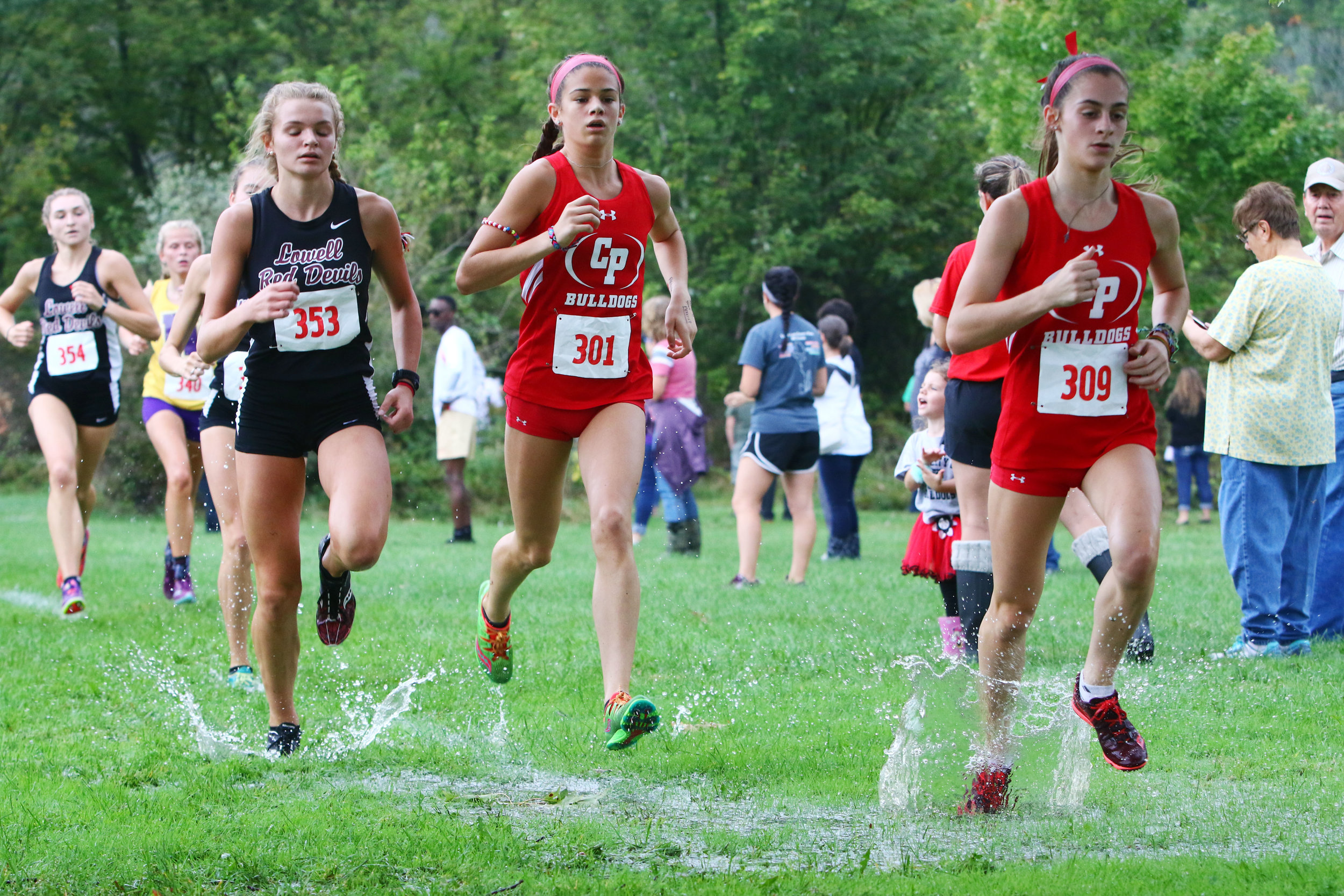 Girls cross country runners, including, from right, Crown Point's Maddie Russin, Jaelyn Burgos and Lowell's Karina James, slosh through the course at Lemon Lake County Park in Crown Point.
