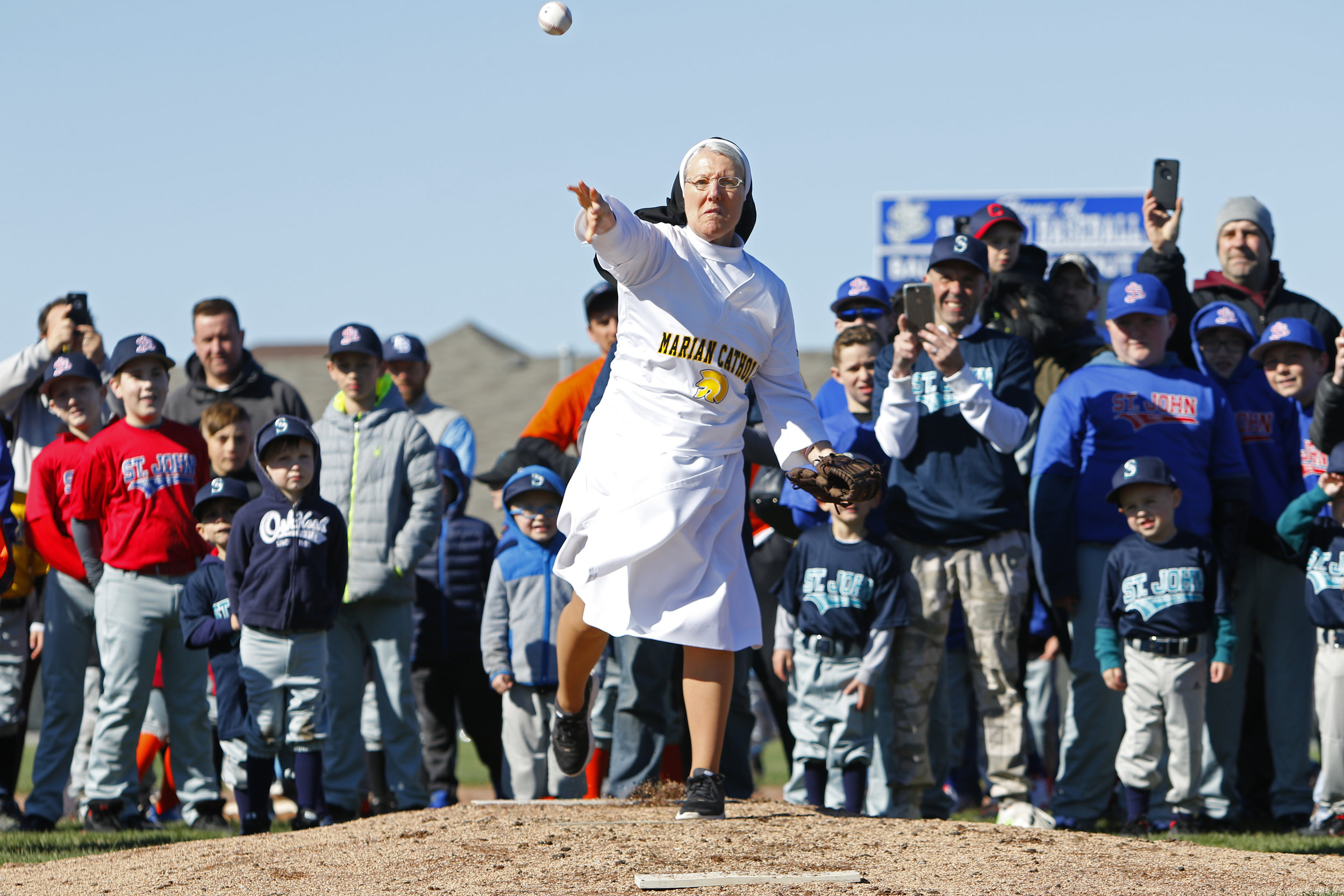 Marian Catholic's Sister Mary Jo Sobieck throws out the first pitch during opening day ceremonies at St. John Youth Baseball's fields in Dyer. Sobieck went viral last year after throwing out the first pitch at a Chicago White Sox game.