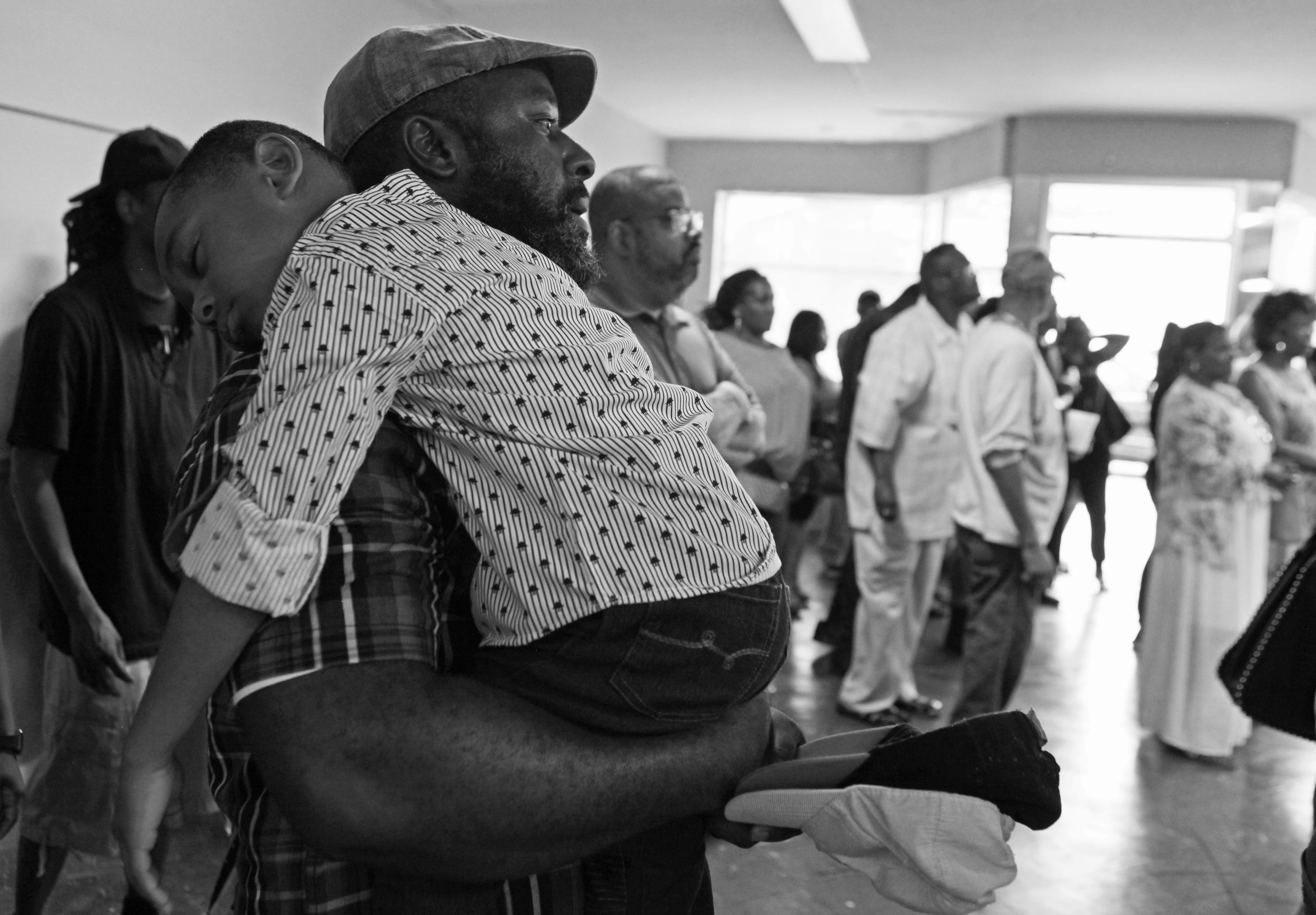 "Ivan Ursery, of Gary, holds his sleeping son, Ivan III, during a ""Can We Talk?"" community outreach meeting hosted by Jerome Prince at his campaign headquarters in Gary."