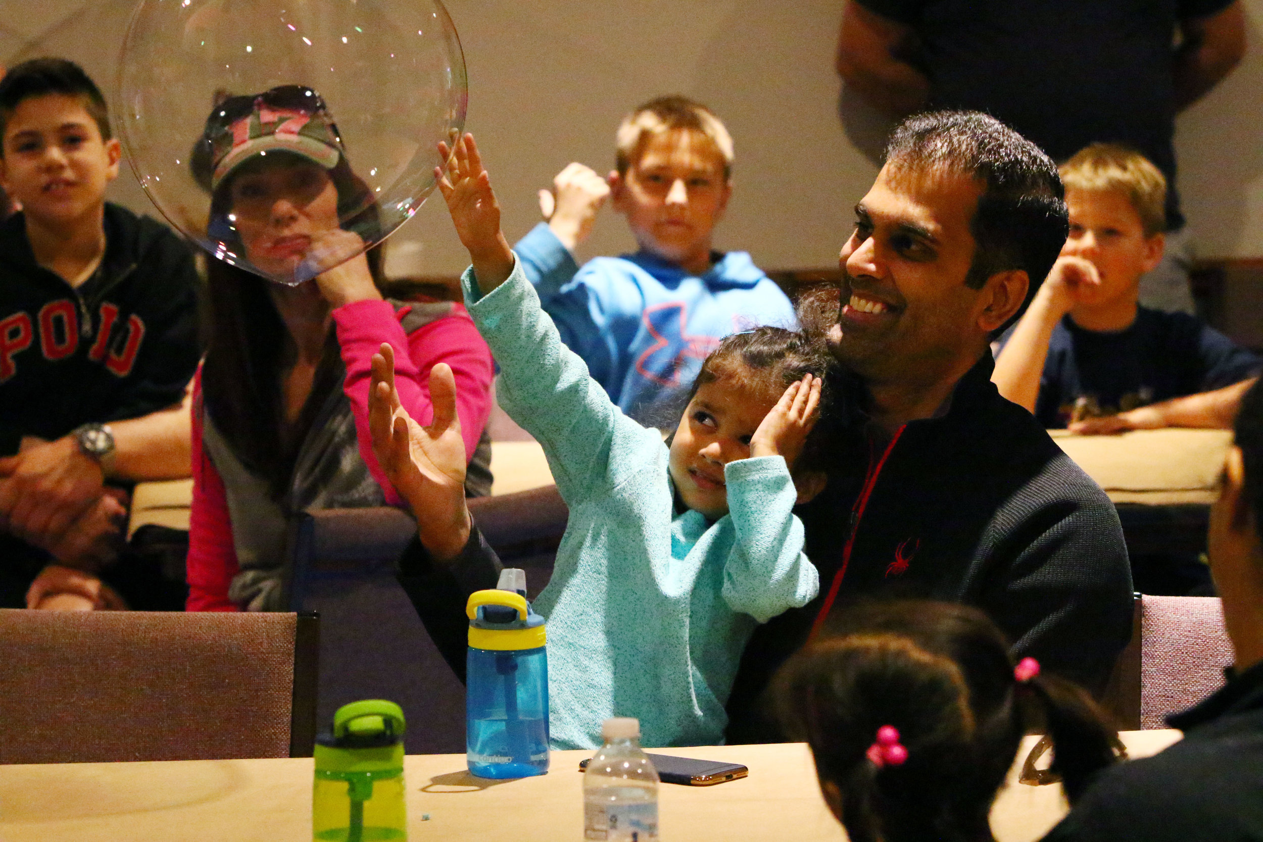 Neel Jain, right, of Chesterton, laughs as his daughter, Sonya, shys away from a bubble floating toward her at the Dunes Learning Center in Chesterton. Families attended a bubble art event led by Mike Bever.