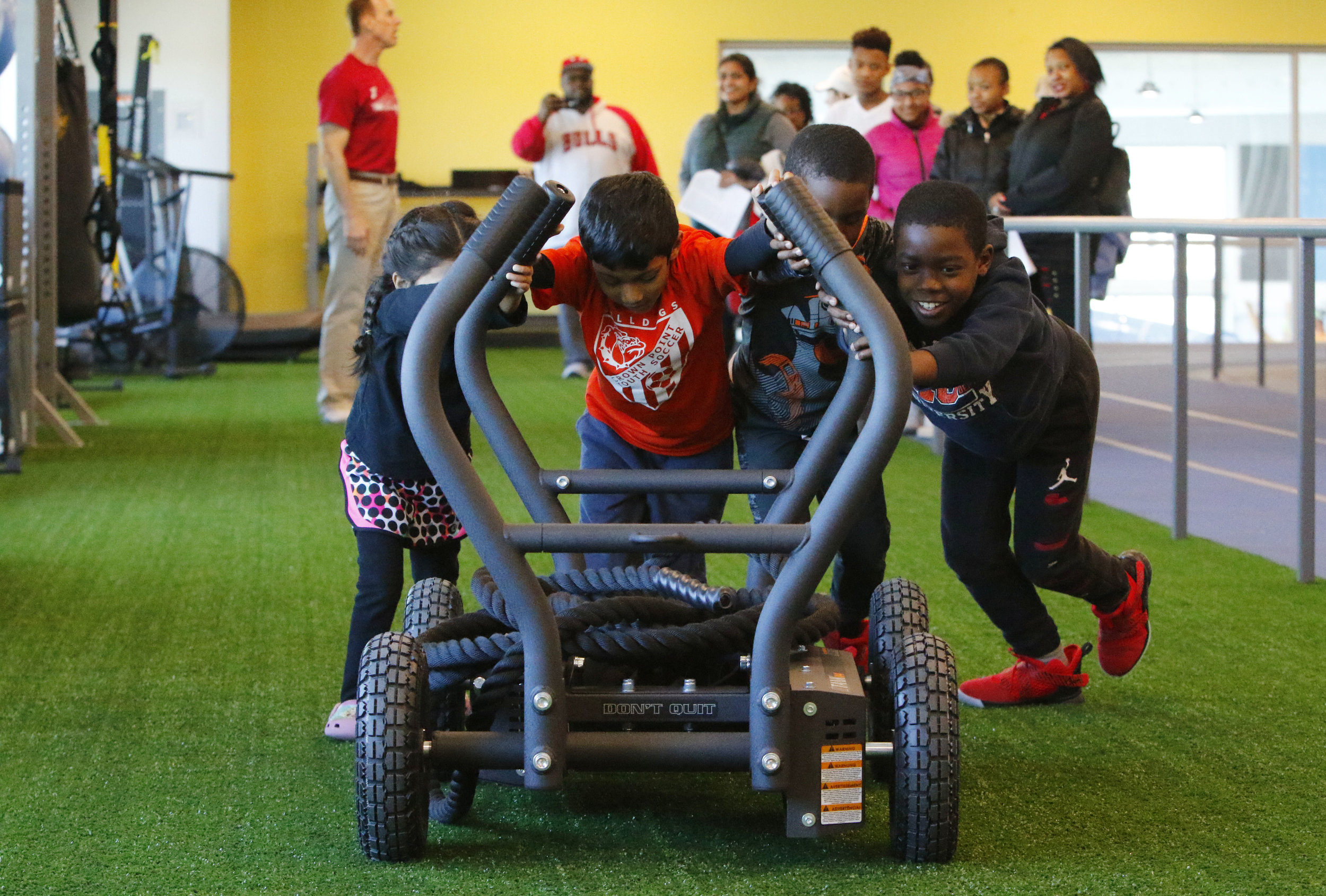Kids join together to push a sled during a tour of the amenities at the Dean and Barbara White Southlake YMCA in Crown Point.