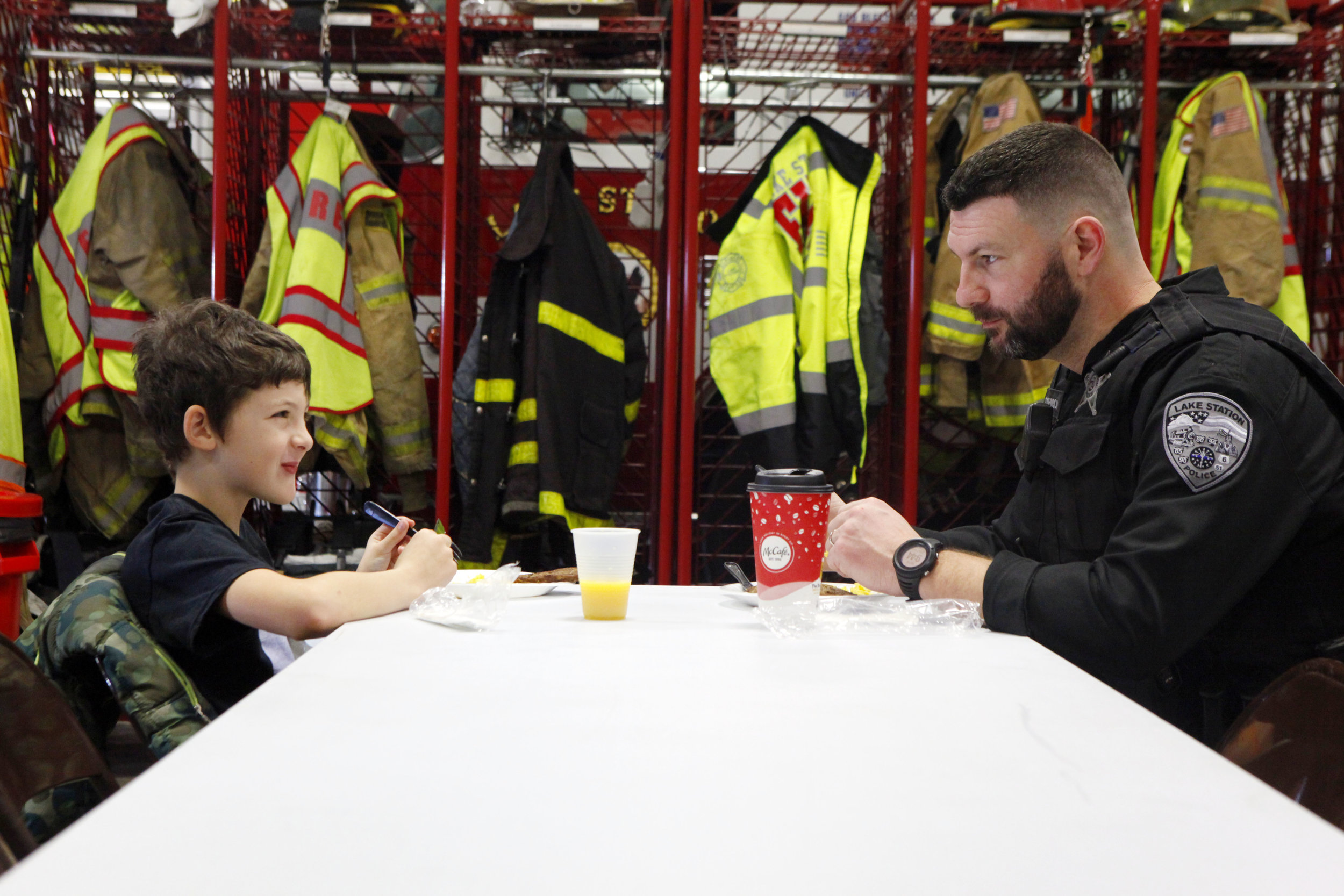 Lake Station Police Chief Dave Johnson, right, shares a conversation and breakfast with Chase Hammons, also of Lake Station, during a holiday youth assistance program hosted by the Fraternal Order of Police Lodge No. 153 at the Lake Station Fire Station.
