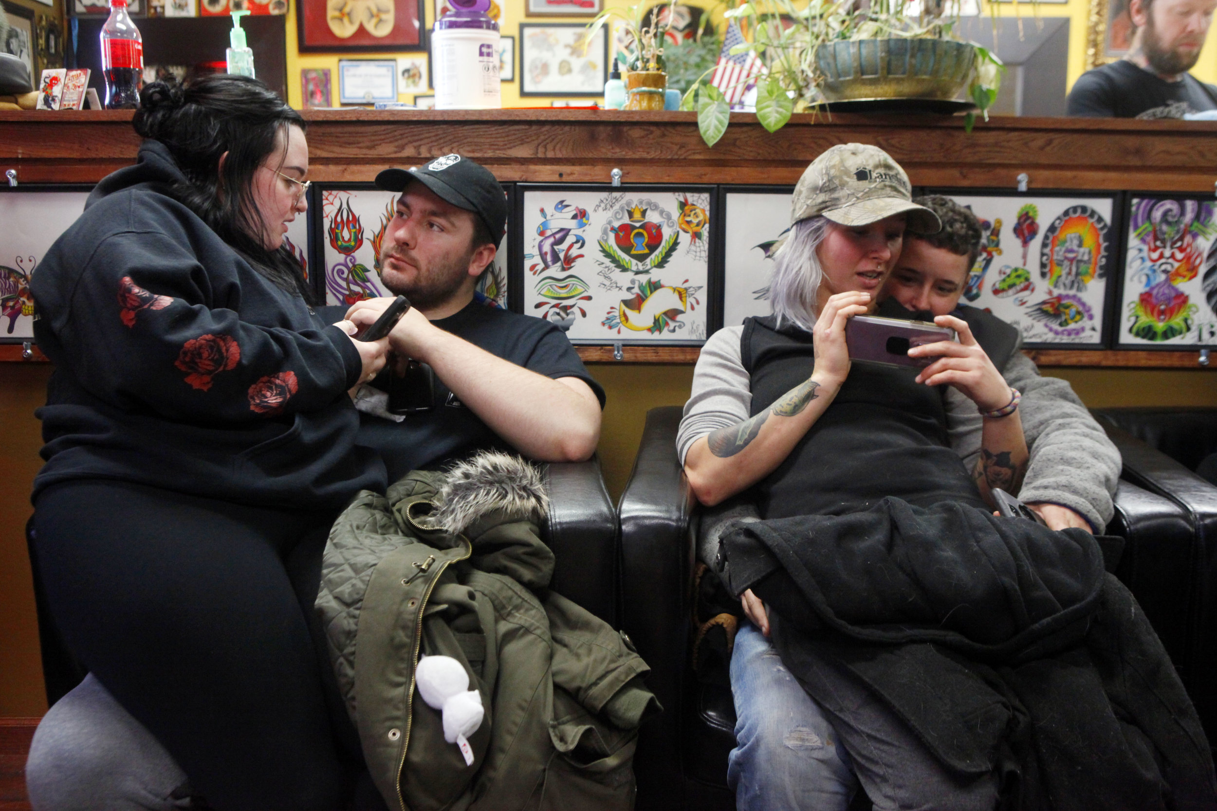 A pair of couples wait their turn to get tattoos at 45th Street Tattoo in Griffith during the business' third annual Toys for Tots event. Pictured to the left are Morgan Weidman, of Chicago and Jacob Sylvester, of Crown Point, and to the right are Amber Jetmund, of Portage, and Boogie Pacheco, also of Portage. A children's toy donation was able to be exchanged for a free tattoo.