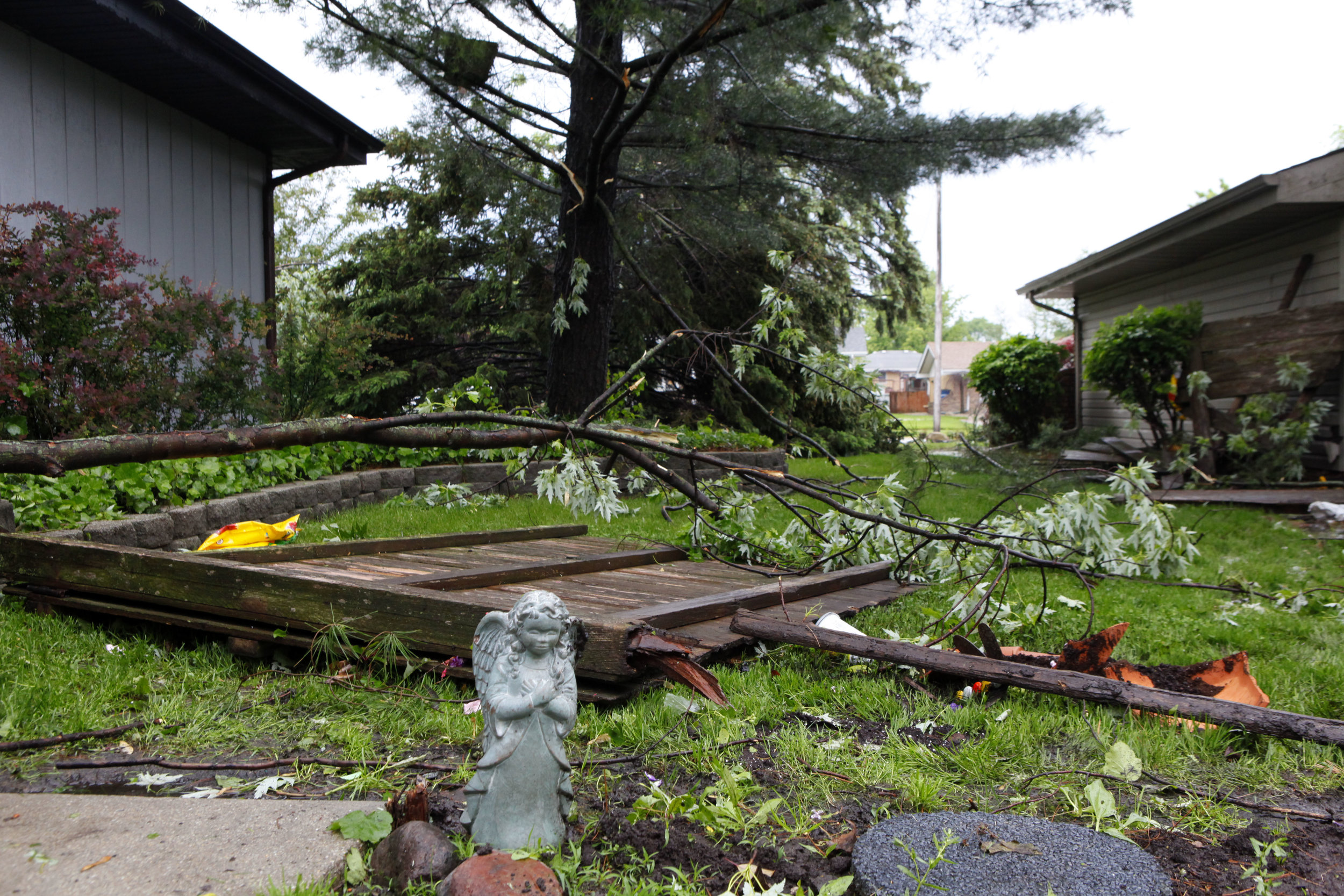 An angel lawn ornament is left standing amid damage to the home of Chris and Judy Artim caused by a tornado in Dyer.