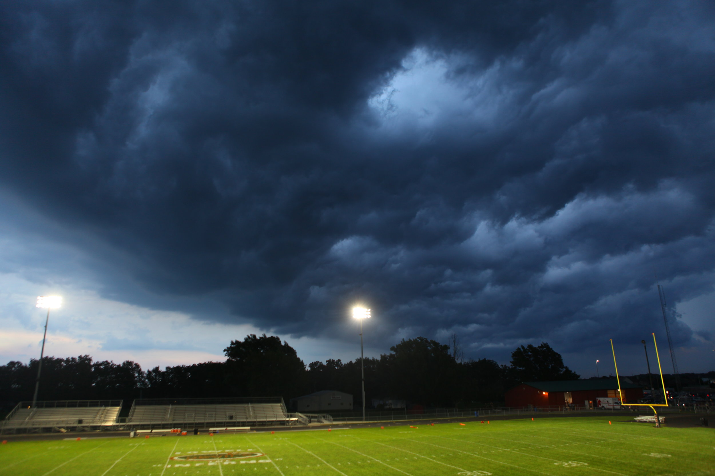 Dark clouds hover over the Inferno at Lowell High School. Lightning and rain brought on a delay before the Red Devils and Morton Governors could take the field.