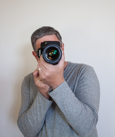 Elbows in tight, left hand hand under the lens.