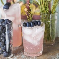 Rosemary Blueberry Smash - Ingredients:- 7-8 blueberries- 1 rosemary spring, stripped- 1 oz. honey syrup- 1 oz. fresh lemon juice, strained- 4 oz. sparkling mineral waterInstructions:Gently muddle blueberries, rosemary leaves, and honey syrup in the bottom of a cocktail shaker. Add lemon juice and shake, covered, with ice vigorously for 10 seconds. Strain through a mesh strainer into a tall glass of fresh ice. Top with sparkling water and stir to incorporate.