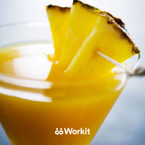 yellow mocktail with pineapple garnish in a martini glass