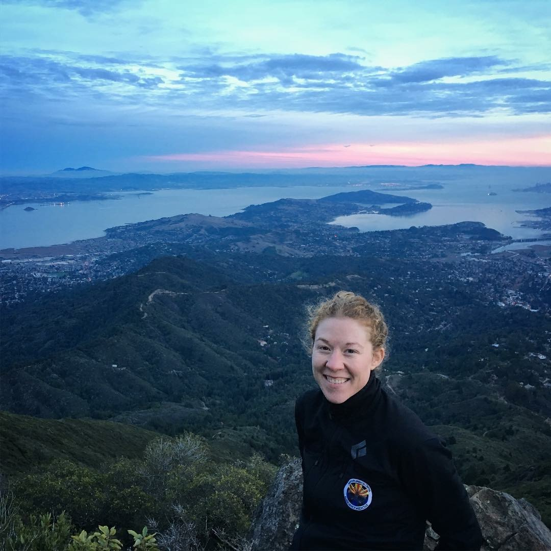 Dr. Melody Glenn standing on a mountain with hills and water behind her