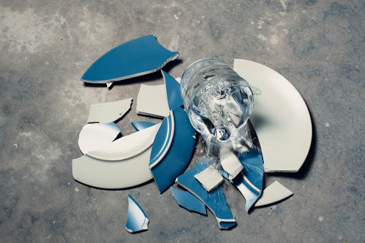 A blue ceramic plate has smashed on a cement floor. A glass of water is falling to join it.
