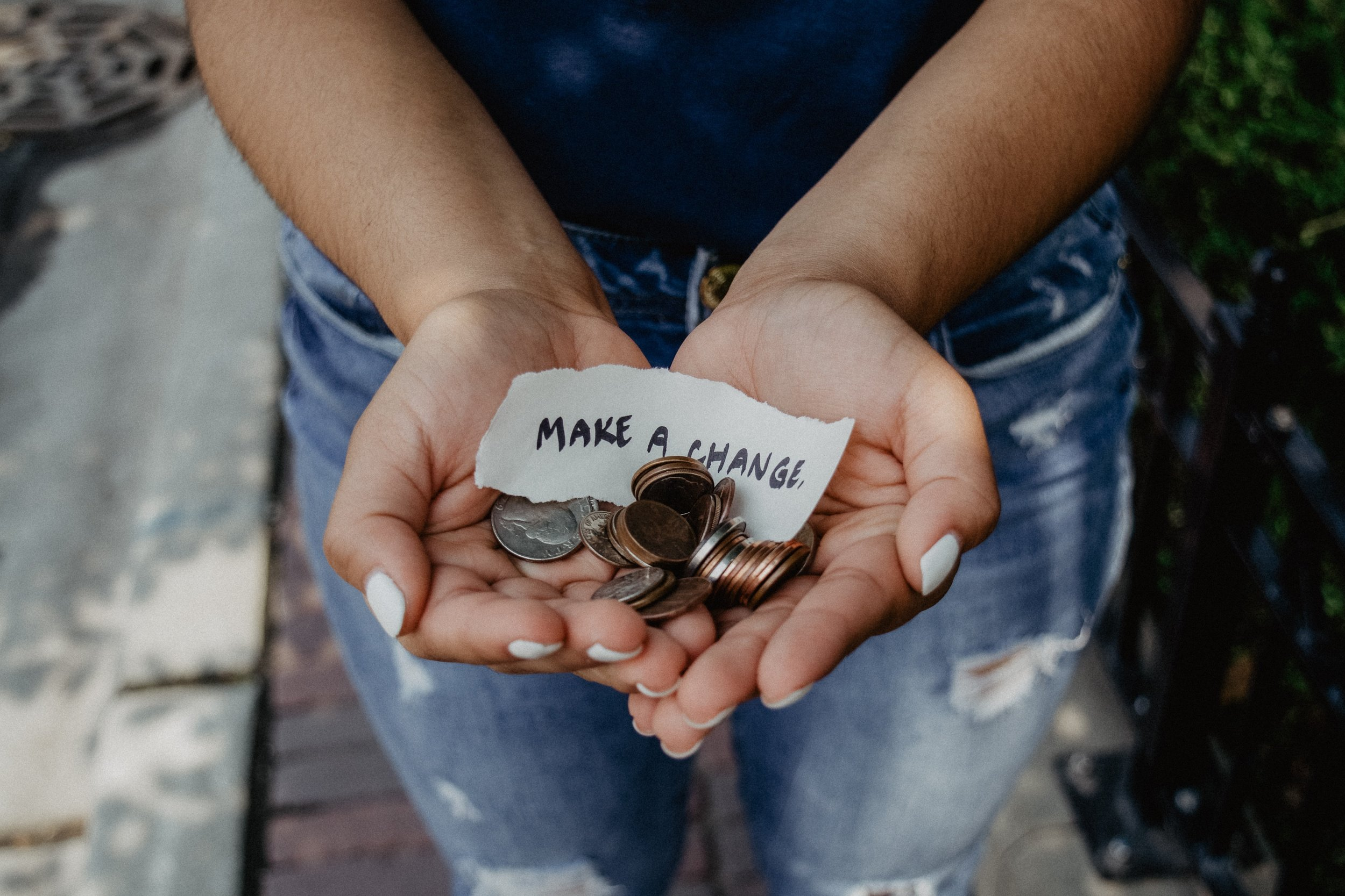 "A woman holds coins in her cupped hands, with a slip of paper that reads, ""Make a change"""